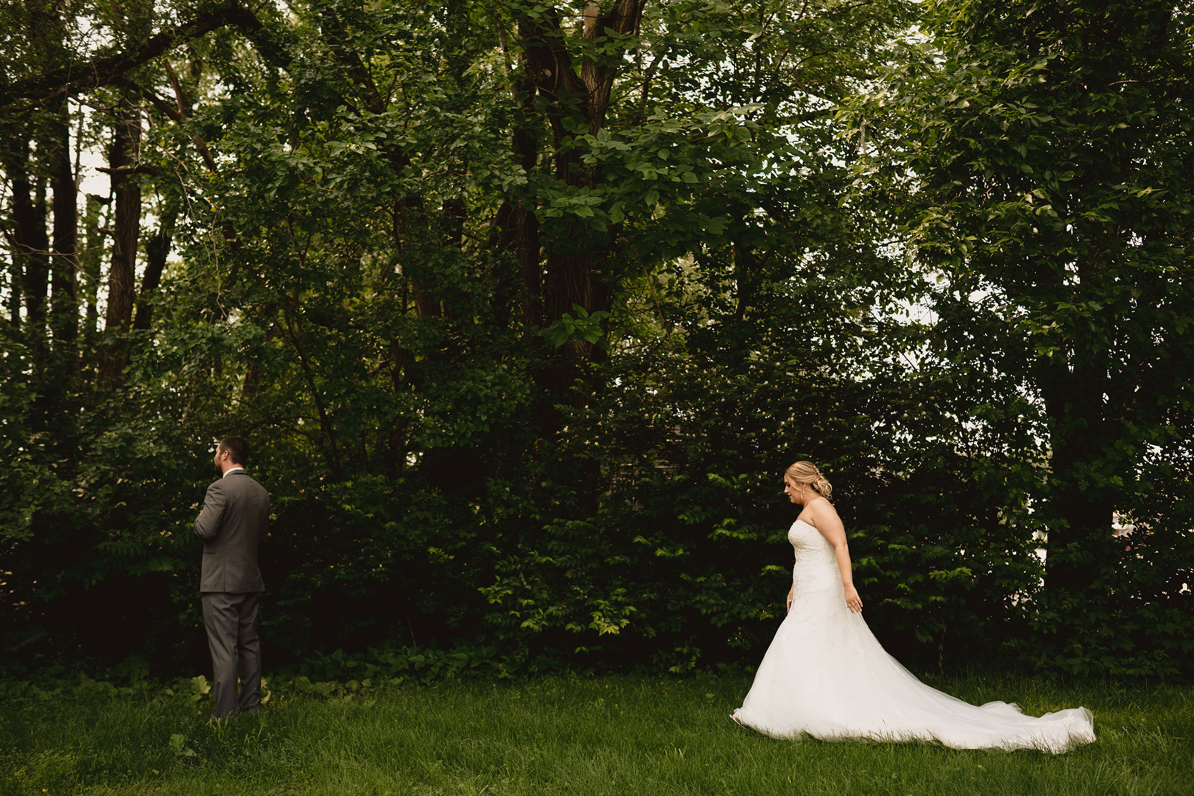 bride-walking-to-groom-for-first-look-decades-event-center-building-desmoines-iowa-raelyn-ramey-photography..jpg