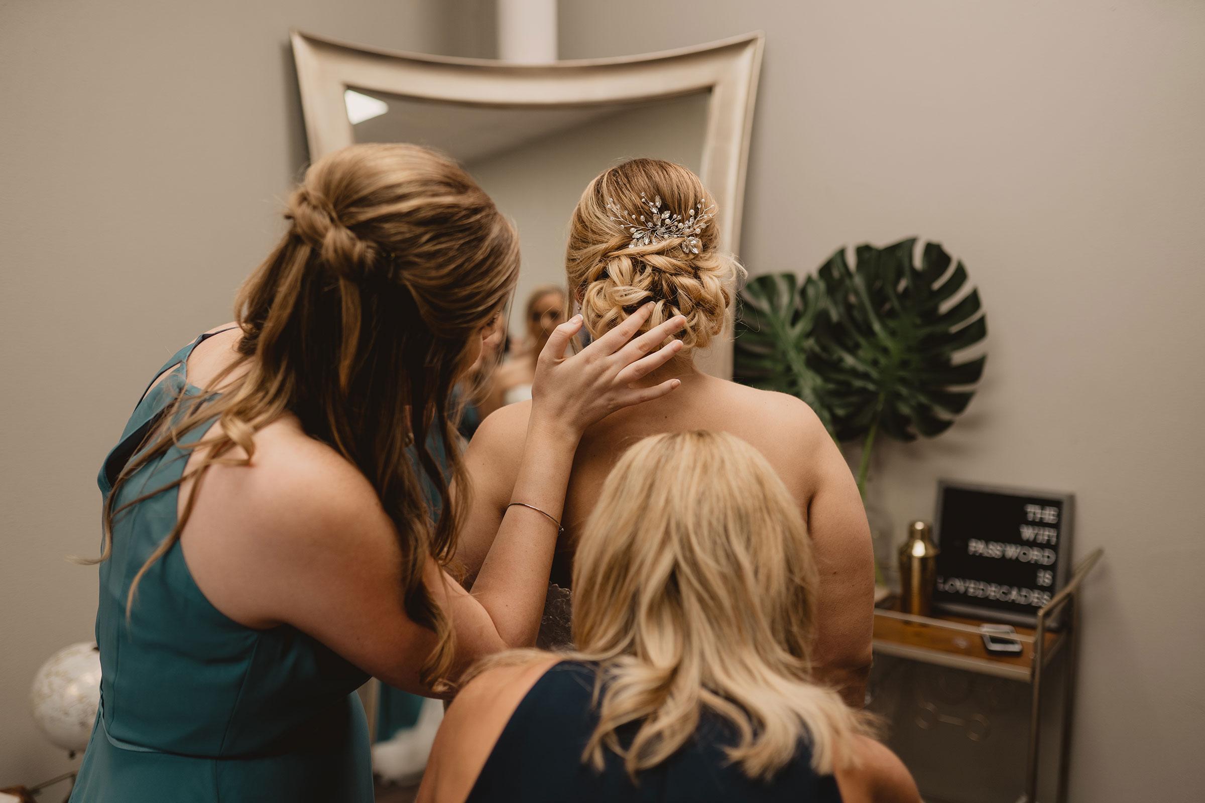 bridemaid-helping-with-hair-decades-event-center-building-desmoines-iowa-raelyn-ramey-photography..jpg
