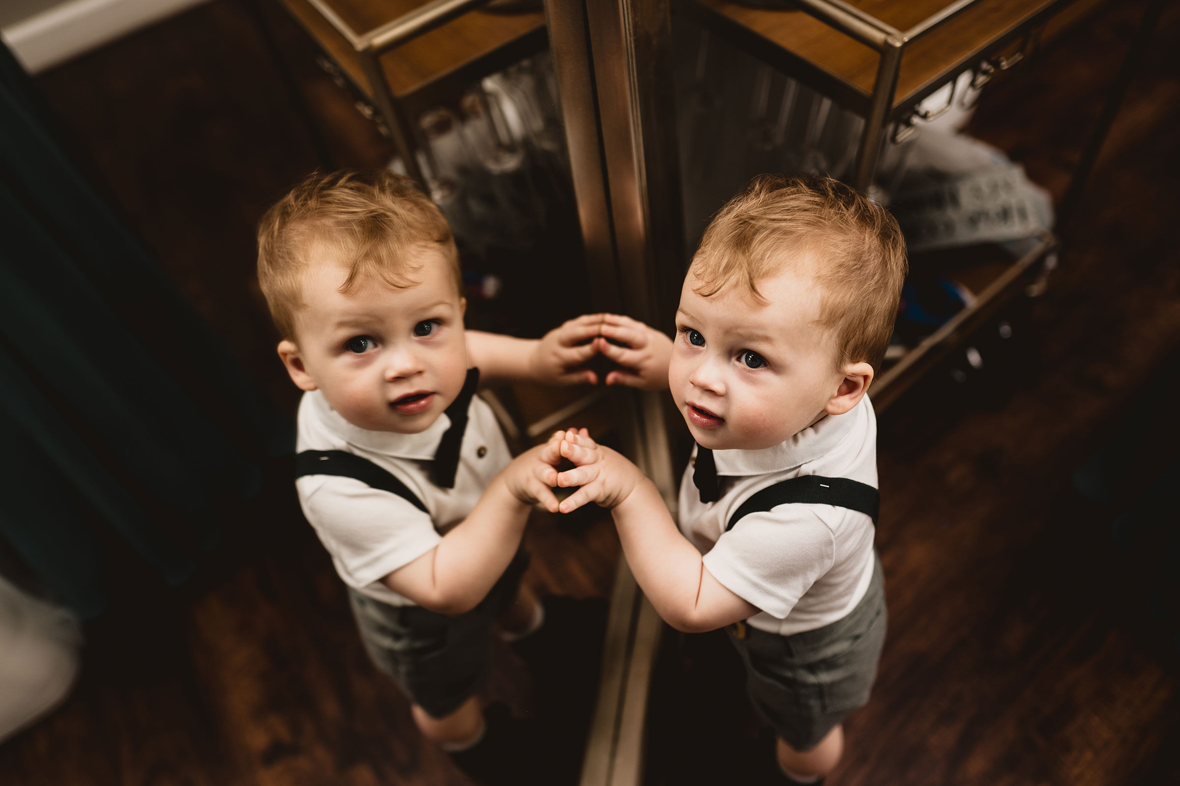 brides-son-looking-at-reflection-in-mirror-decades-event-center-building-desmoines-iowa-raelyn-ramey-photography..jpg