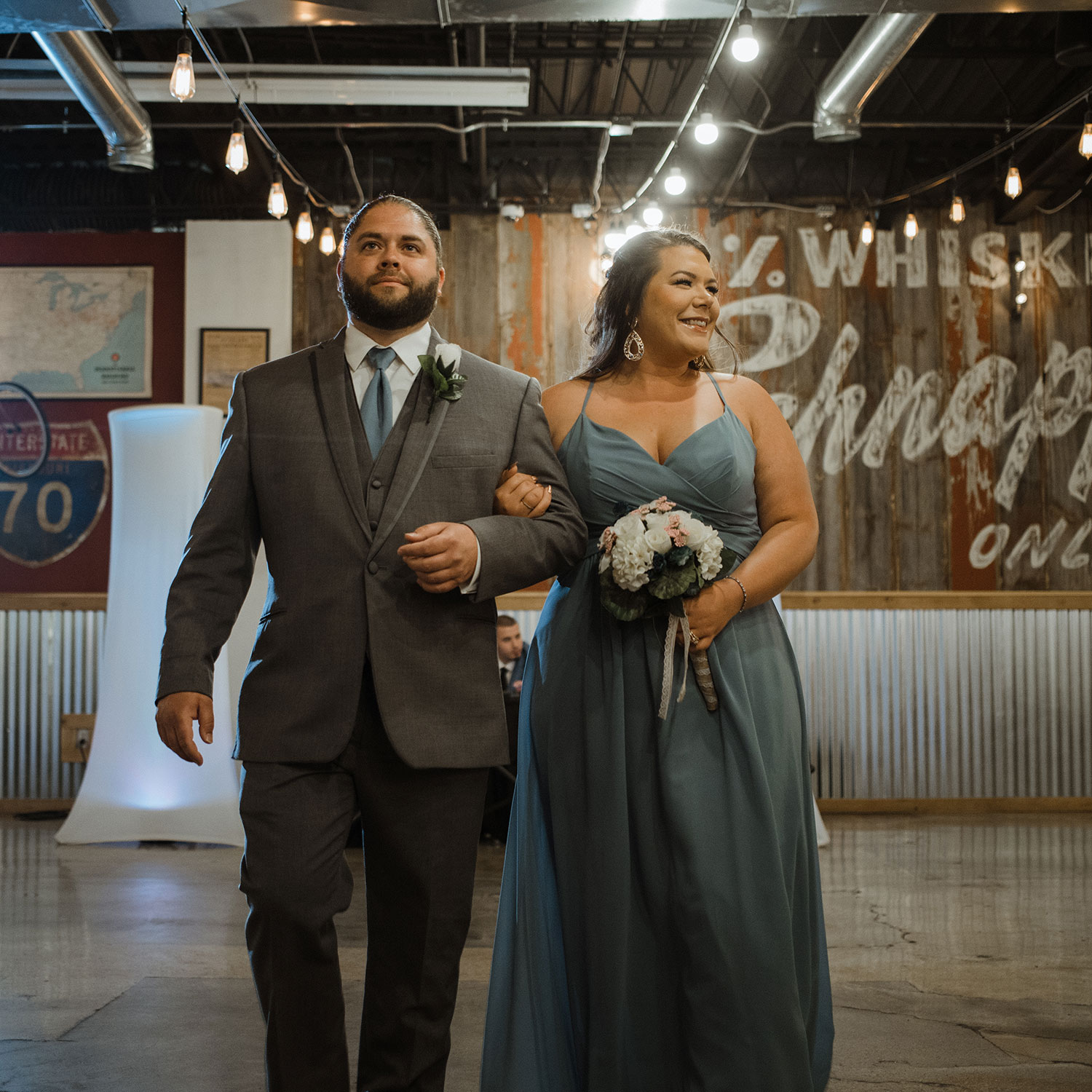 bridesmaid-and-groomsmen-first-walking-down-aisle-decades-event-center-building-desmoines-iowa-raelyn-ramey-photography..jpg