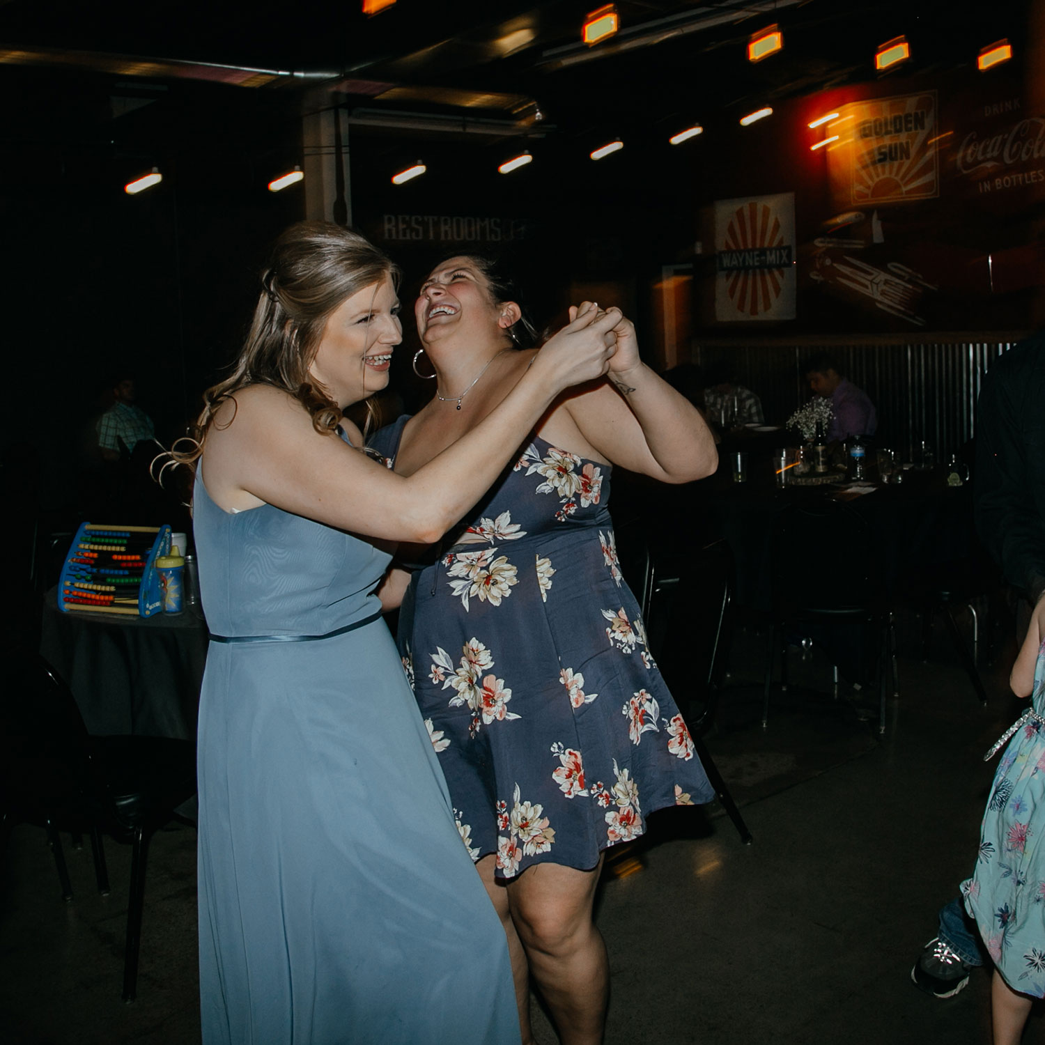 bridesmaid-dancing-decades-event-center-building-desmoines-iowa-raelyn-ramey-photography..jpg
