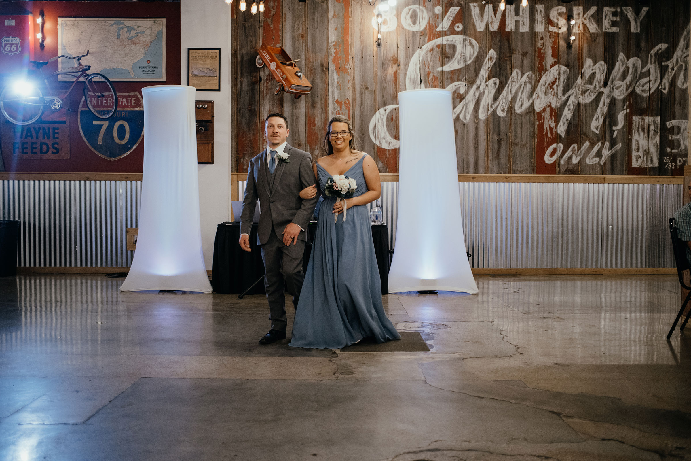 bridesmaid-and-groomsmen-walking-smiling-decades-event-center-building-desmoines-iowa-raelyn-ramey-photography..jpg