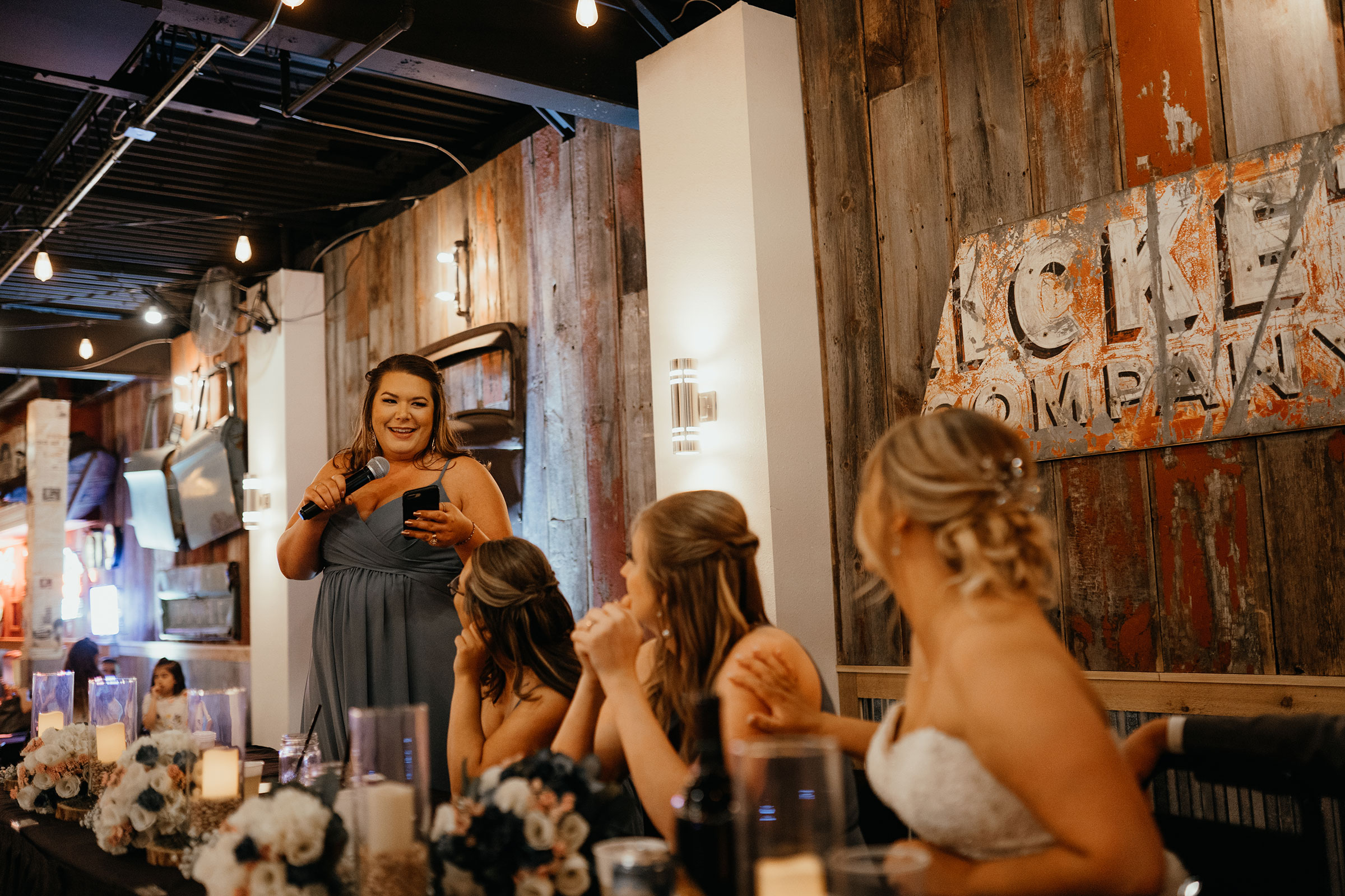 bridesmaid-giving-speech-decades-event-center-building-desmoines-iowa-raelyn-ramey-photography..jpg