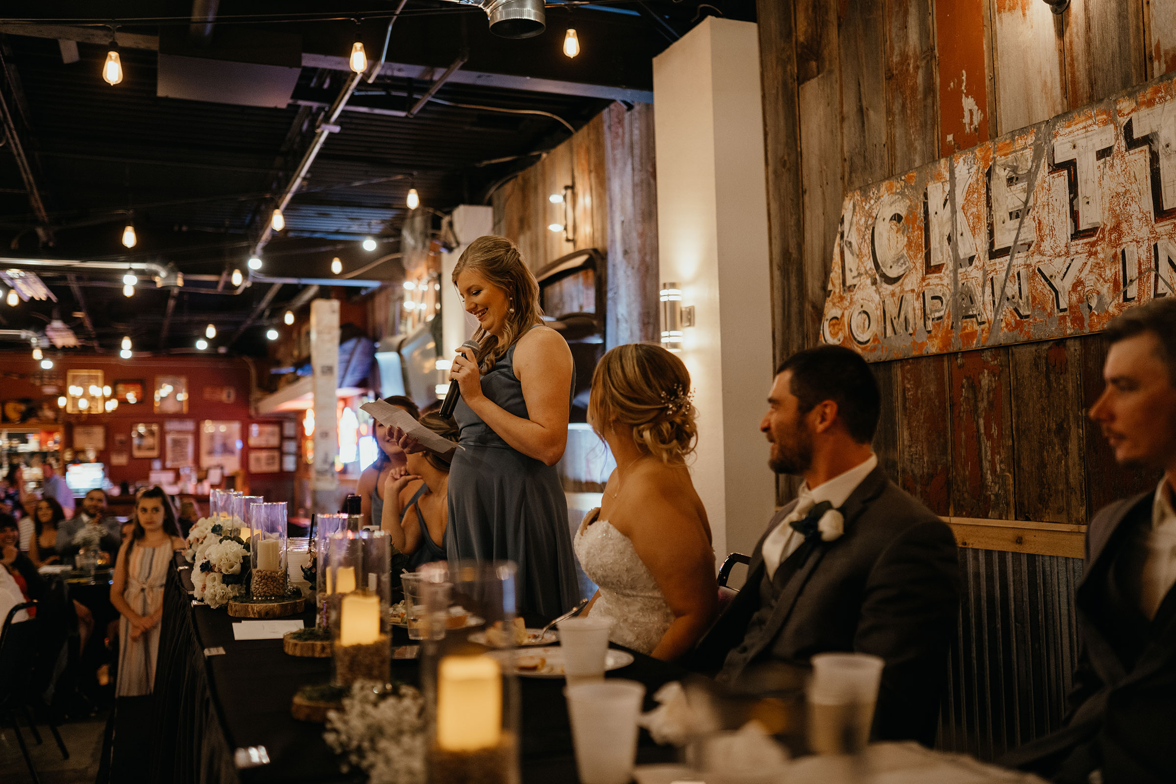 bridesmaid-laughing-during-speech-decades-event-center-building-desmoines-iowa-raelyn-ramey-photography..jpg