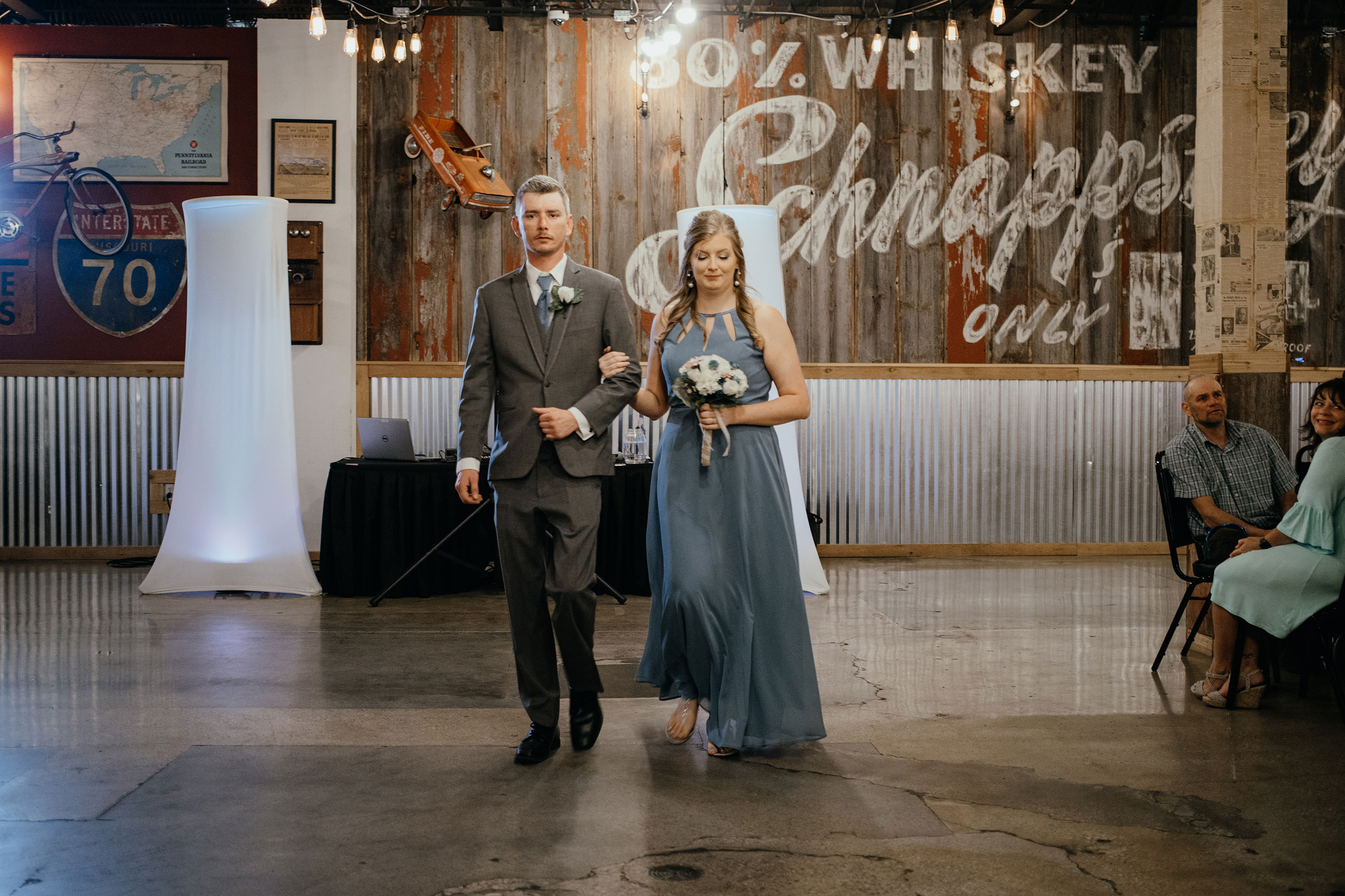 bridesmaid-walking-with-groomsmen-looking-down-decades-event-center-building-desmoines-iowa-raelyn-ramey-photography..jpg