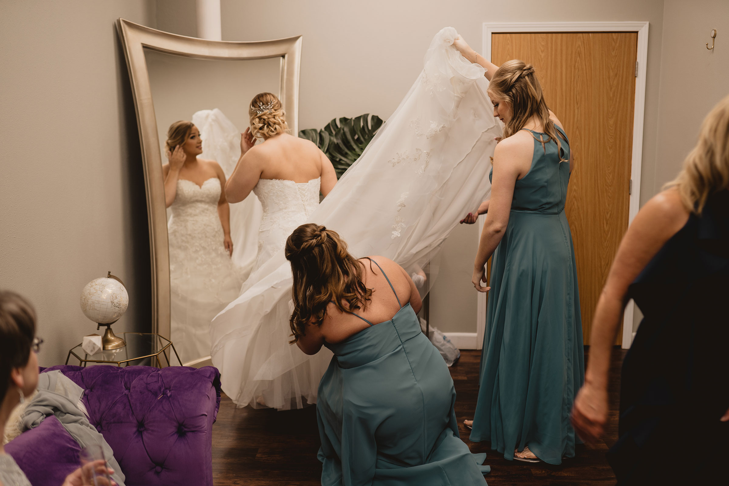 bridesmaids-fluffing-dress-getting-ready-decades-event-center-building-desmoines-iowa-raelyn-ramey-photography..jpg