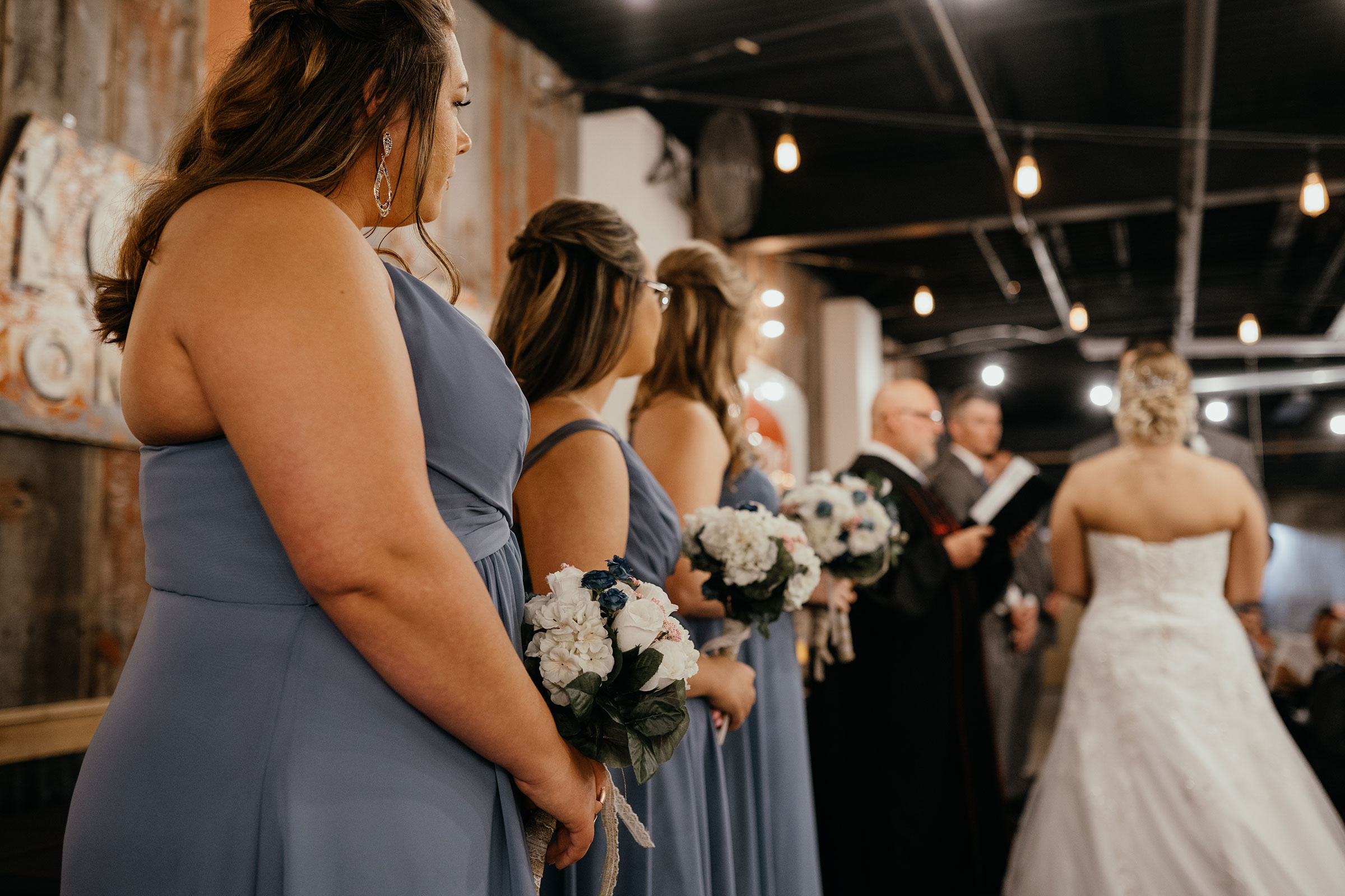 bridesmaids-standing-up-at-ceremony-decades-event-center-building-desmoines-iowa-raelyn-ramey-photography..jpg