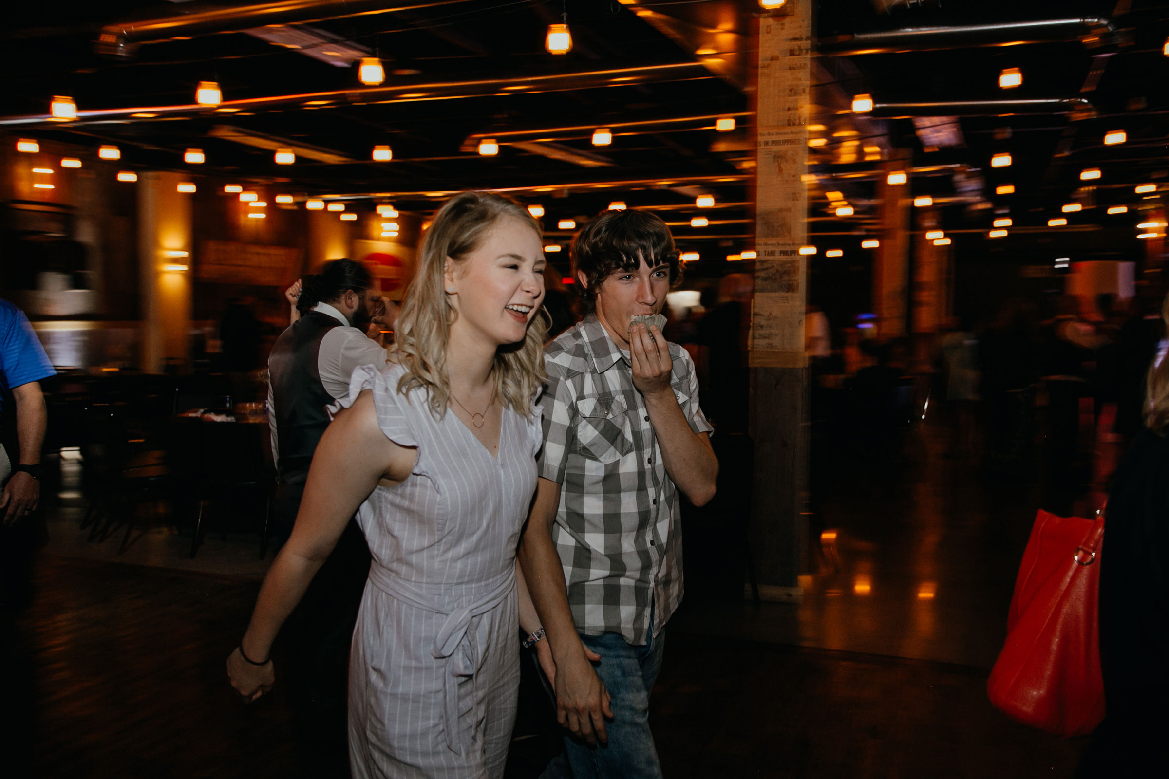 couple-walking-while-eating-cupcake-decades-event-center-building-desmoines-iowa-raelyn-ramey-photography..jpg