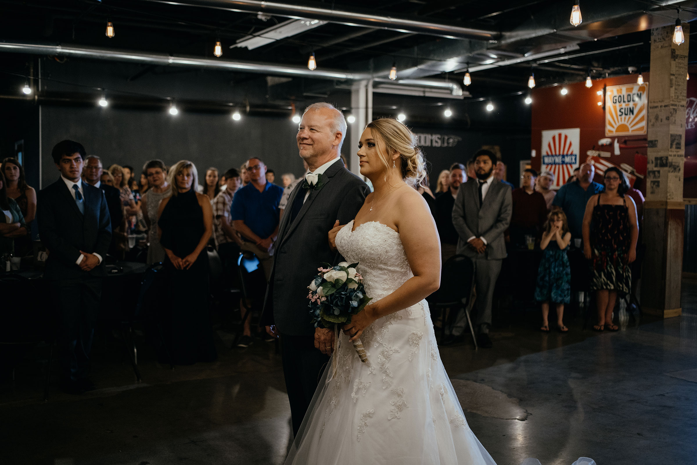 dad-walking-bride-down-aisle-decades-event-center-building-desmoines-iowa-raelyn-ramey-photography..jpg