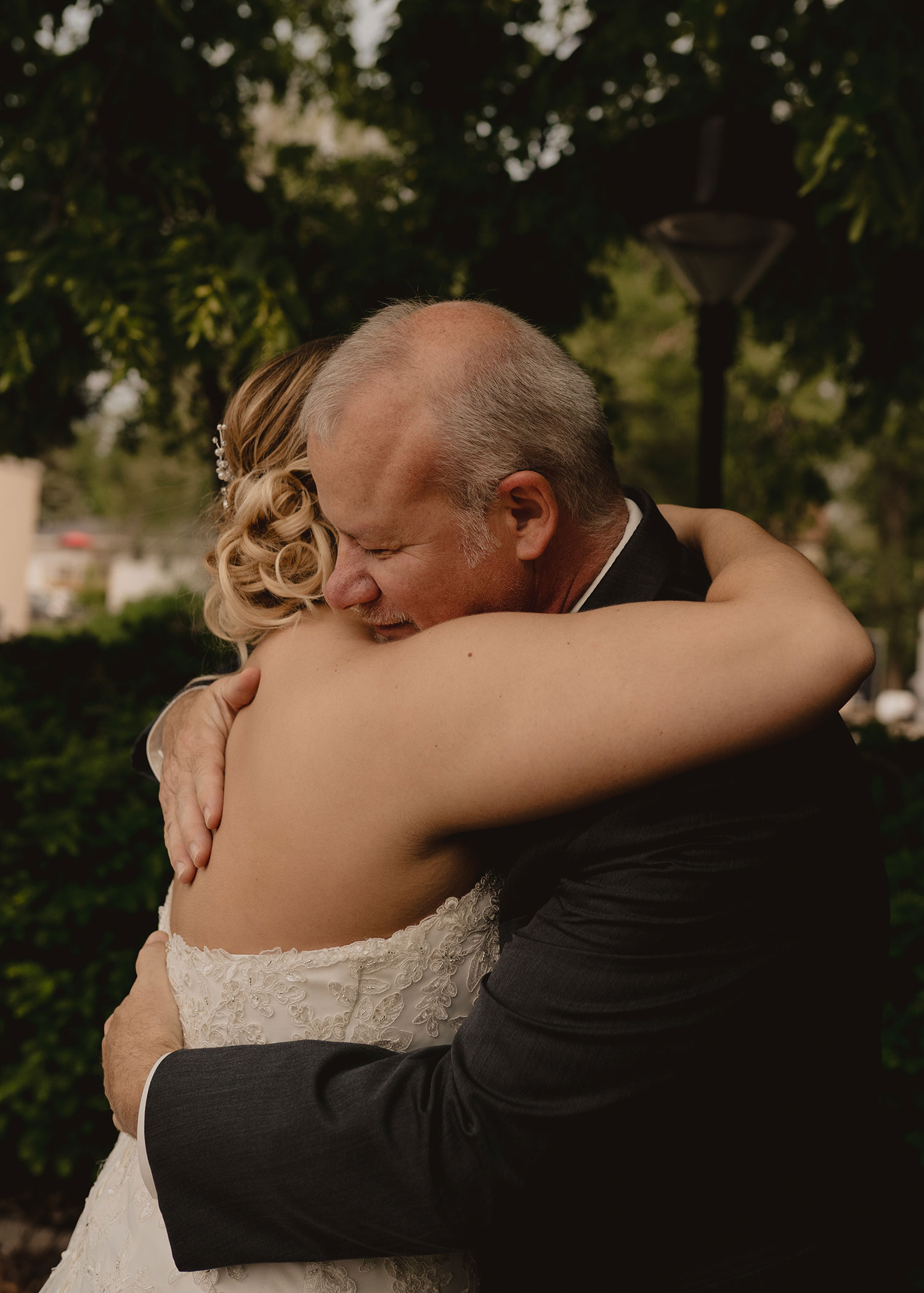 father-hugging-bride-decades-event-center-building-desmoines-iowa-raelyn-ramey-photography..jpg