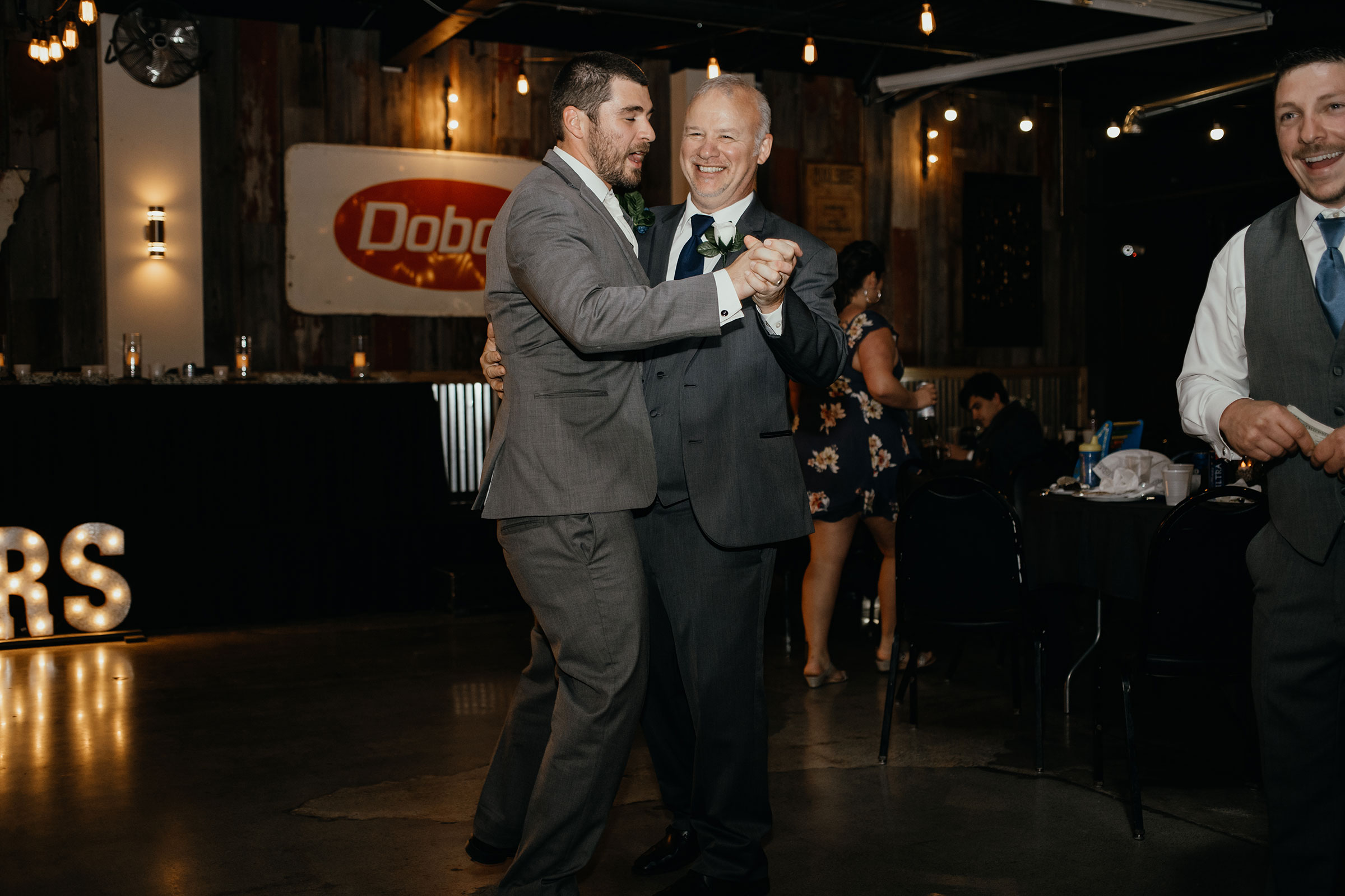 father-of-bride-dancing-with-groom-decades-event-center-building-desmoines-iowa-raelyn-ramey-photography..jpg