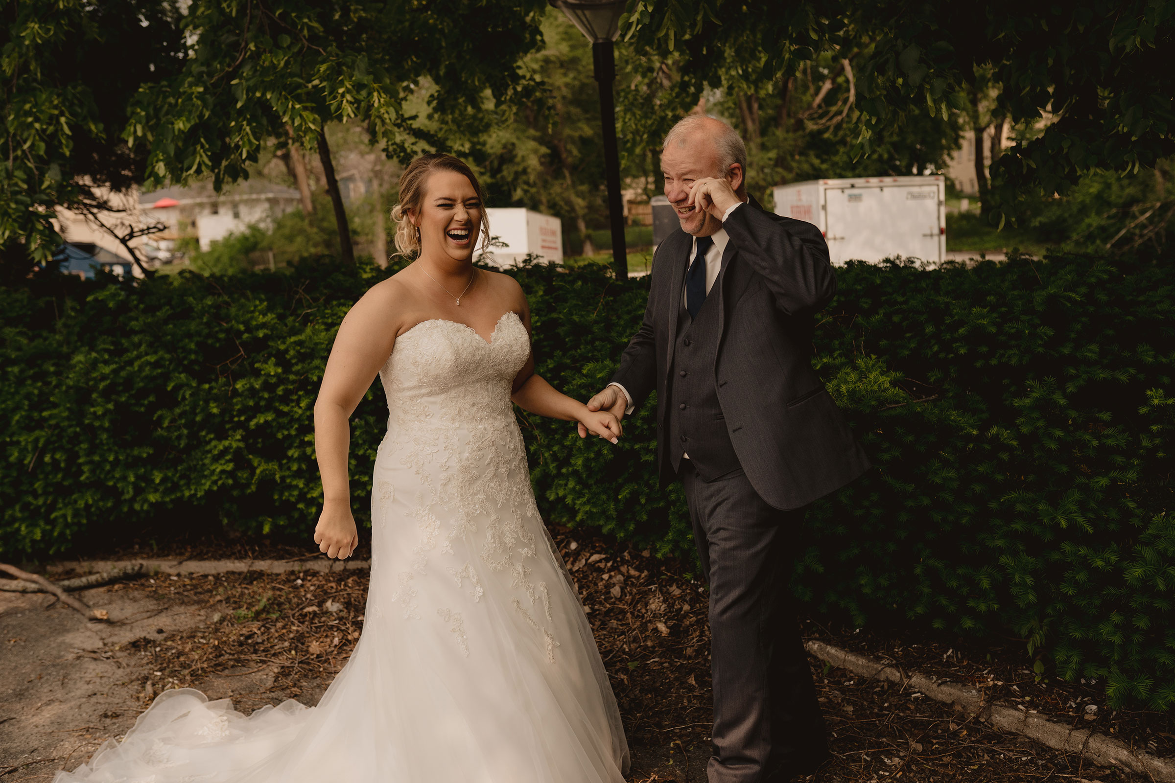 father-of-bride-wiping-tears-from-first-look-decades-event-center-building-desmoines-iowa-raelyn-ramey-photography..jpg
