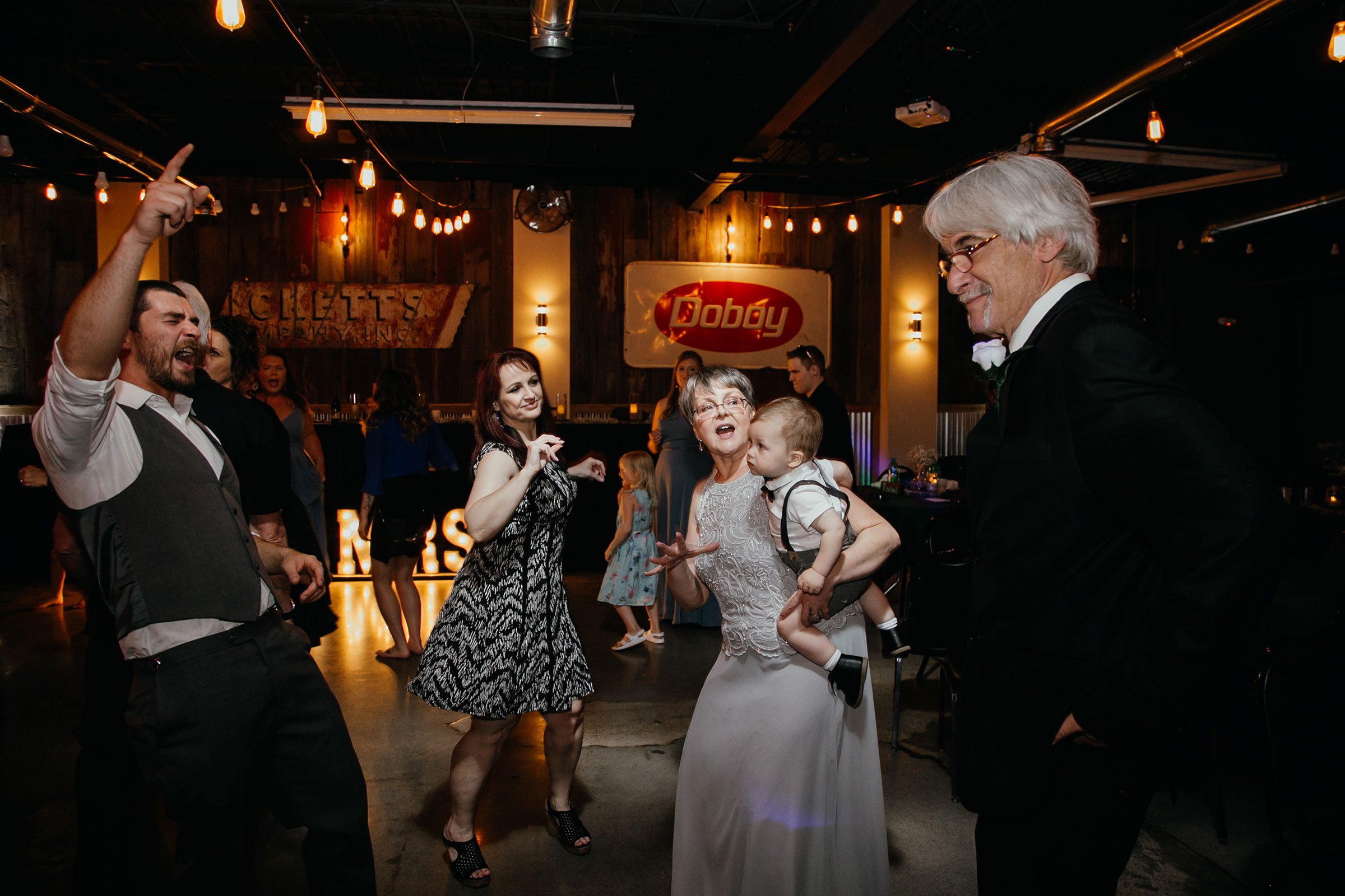 groom-and-parents-dancing-decades-event-center-building-desmoines-iowa-raelyn-ramey-photography..jpg