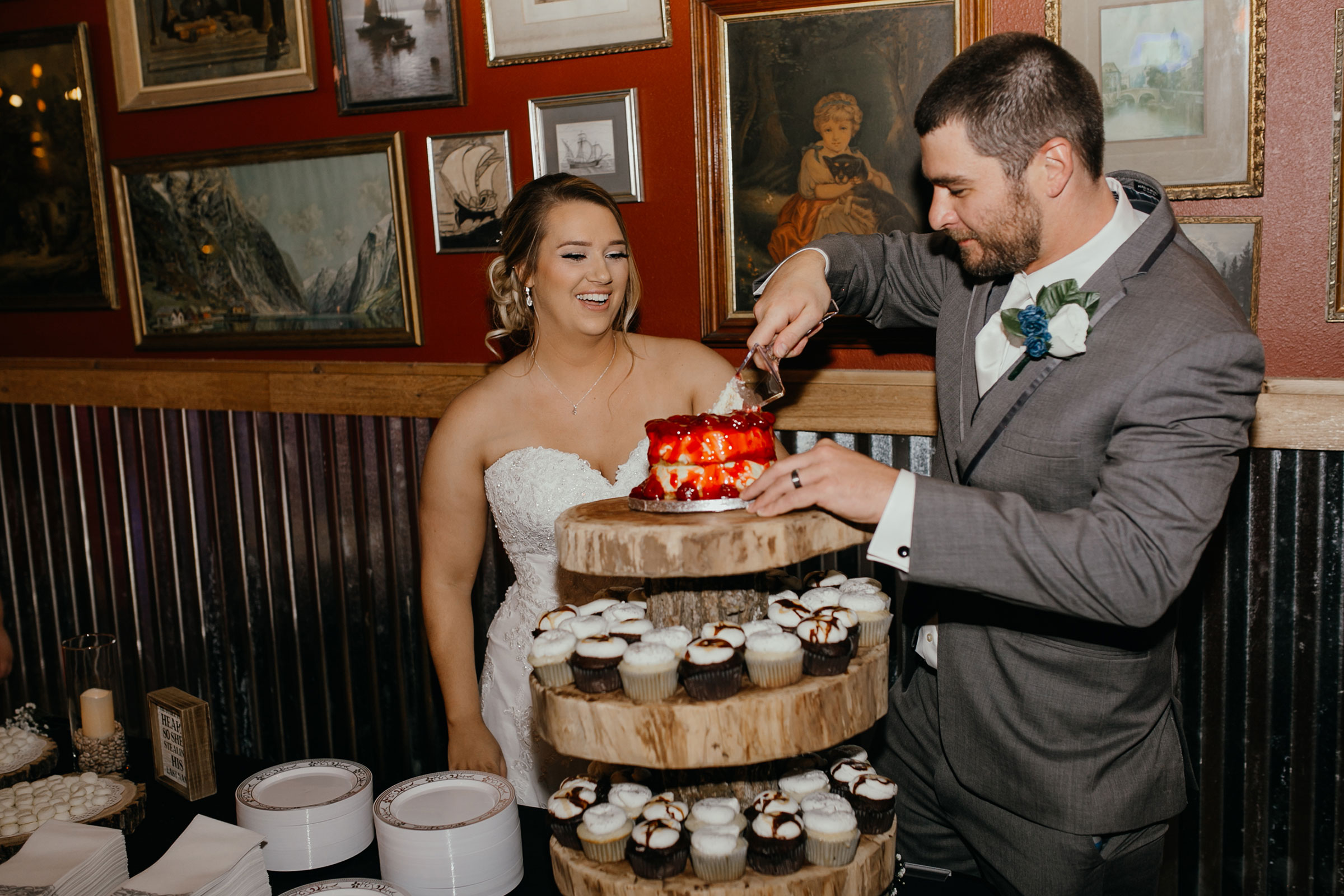 groom-cutting-cake-decades-event-center-building-desmoines-iowa-raelyn-ramey-photography..jpg