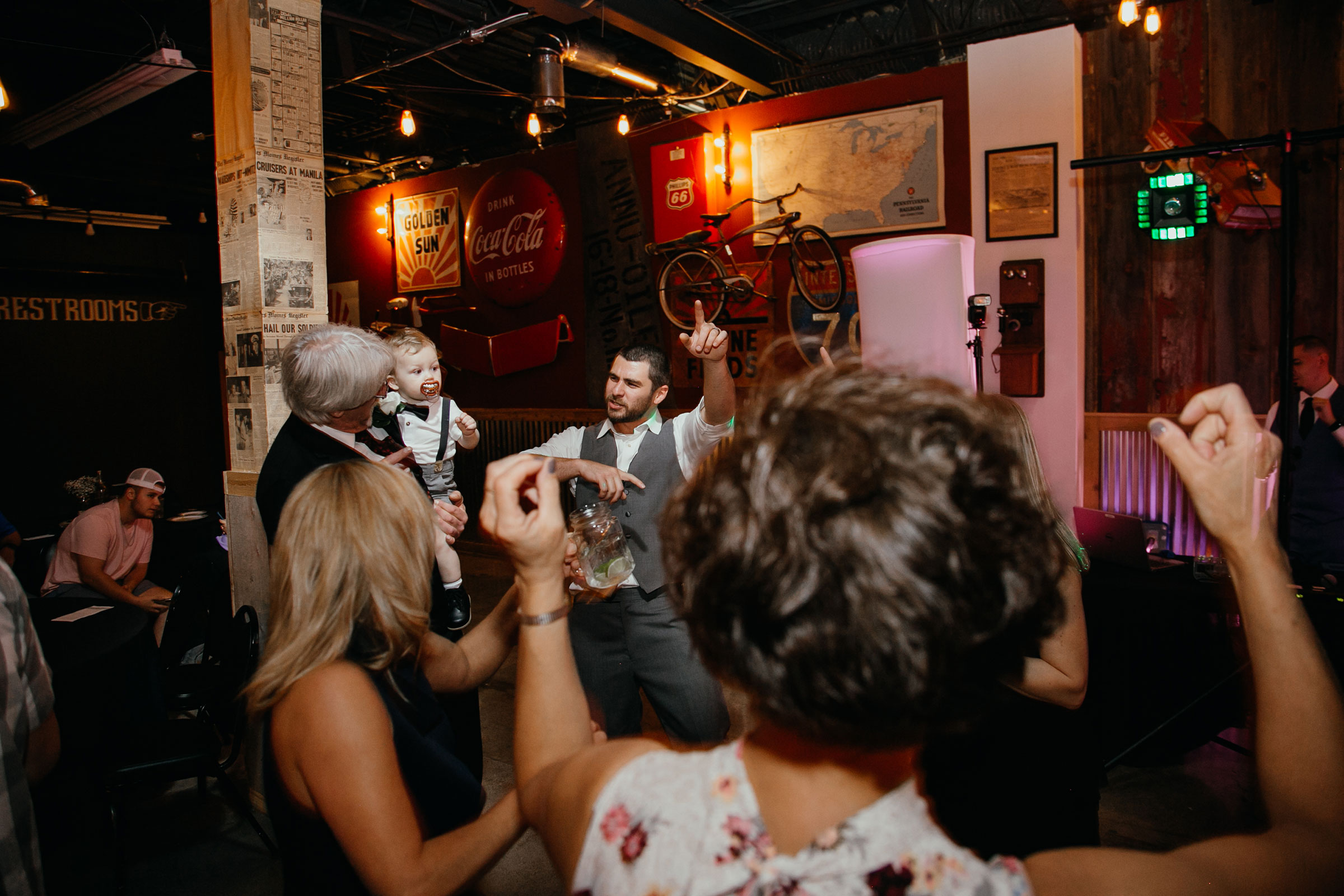 groom-dancing-with-son-and-guests-decades-event-center-building-desmoines-iowa-raelyn-ramey-photography..jpg