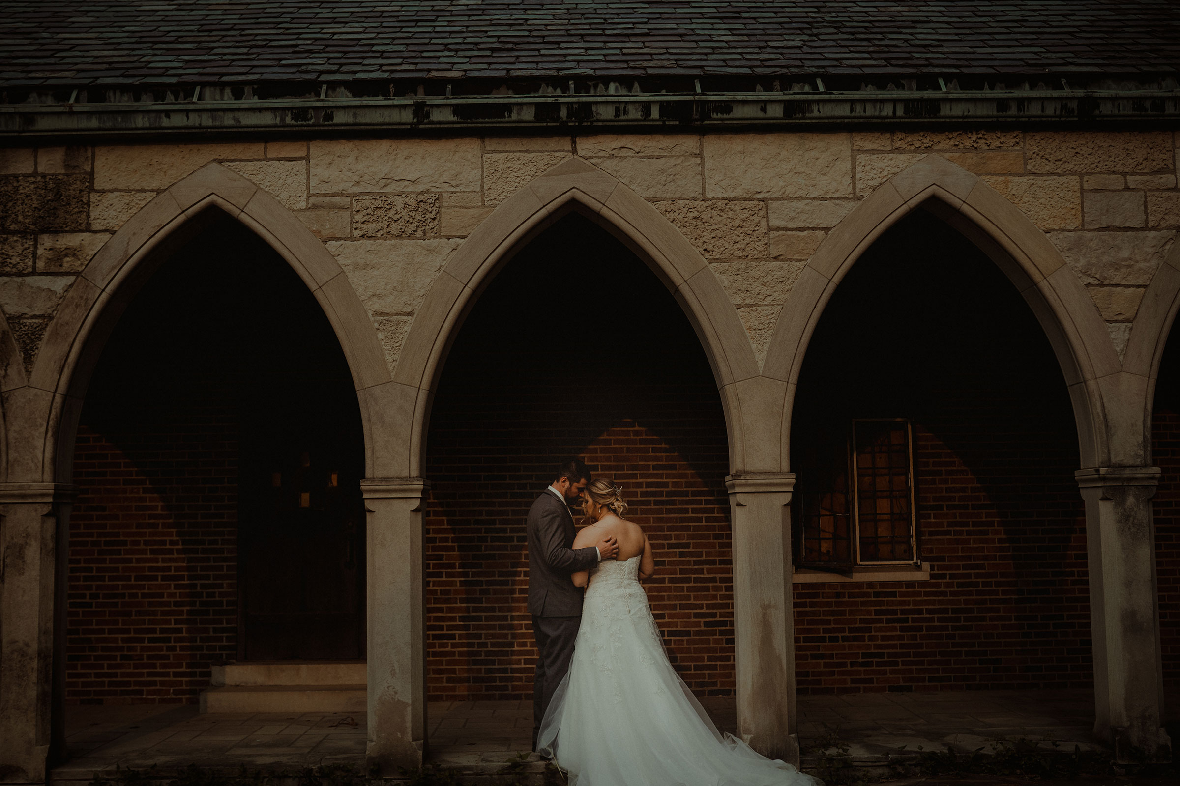 groom-holding-bride-under-church-archway-decades-event-center-building-desmoines-iowa-raelyn-ramey-photography..jpg