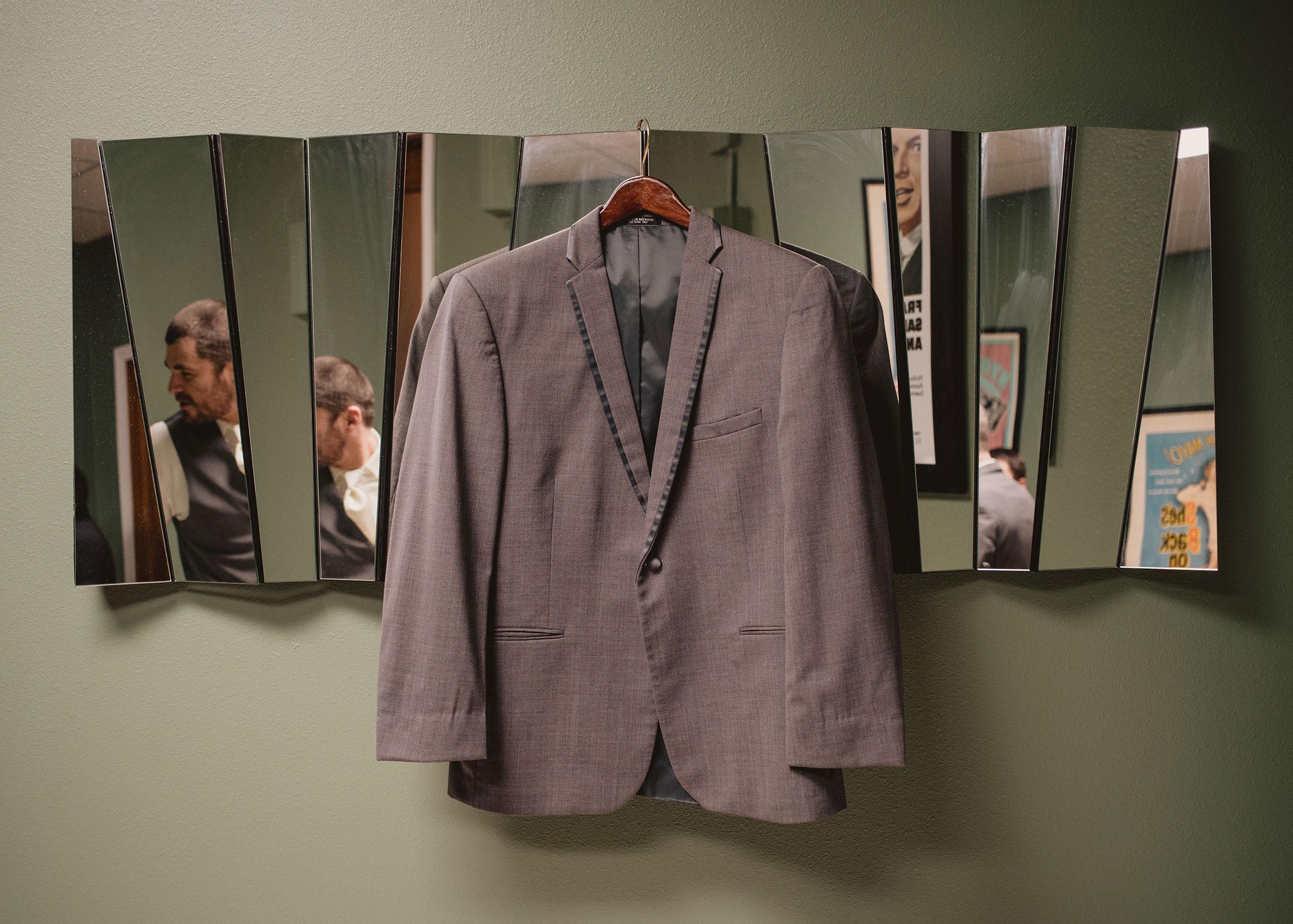 groom-jacket-hanging-on-mirror-decades-event-center-building-desmoines-iowa-raelyn-ramey-photography..jpg