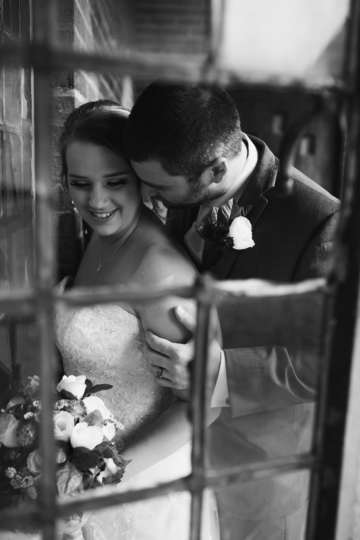 groom-kissing-and-holding-bride-decades-event-center-building-desmoines-iowa-raelyn-ramey-photography..jpg