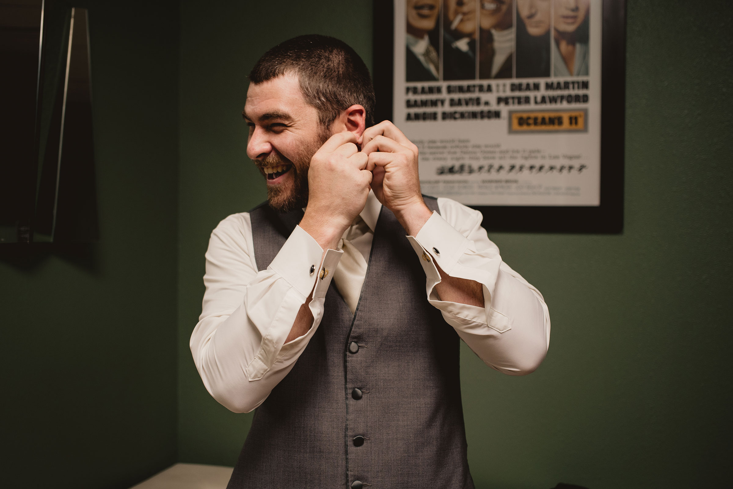 groom-laughing-about-earrings-decades-event-center-building-desmoines-iowa-raelyn-ramey-photography..jpg