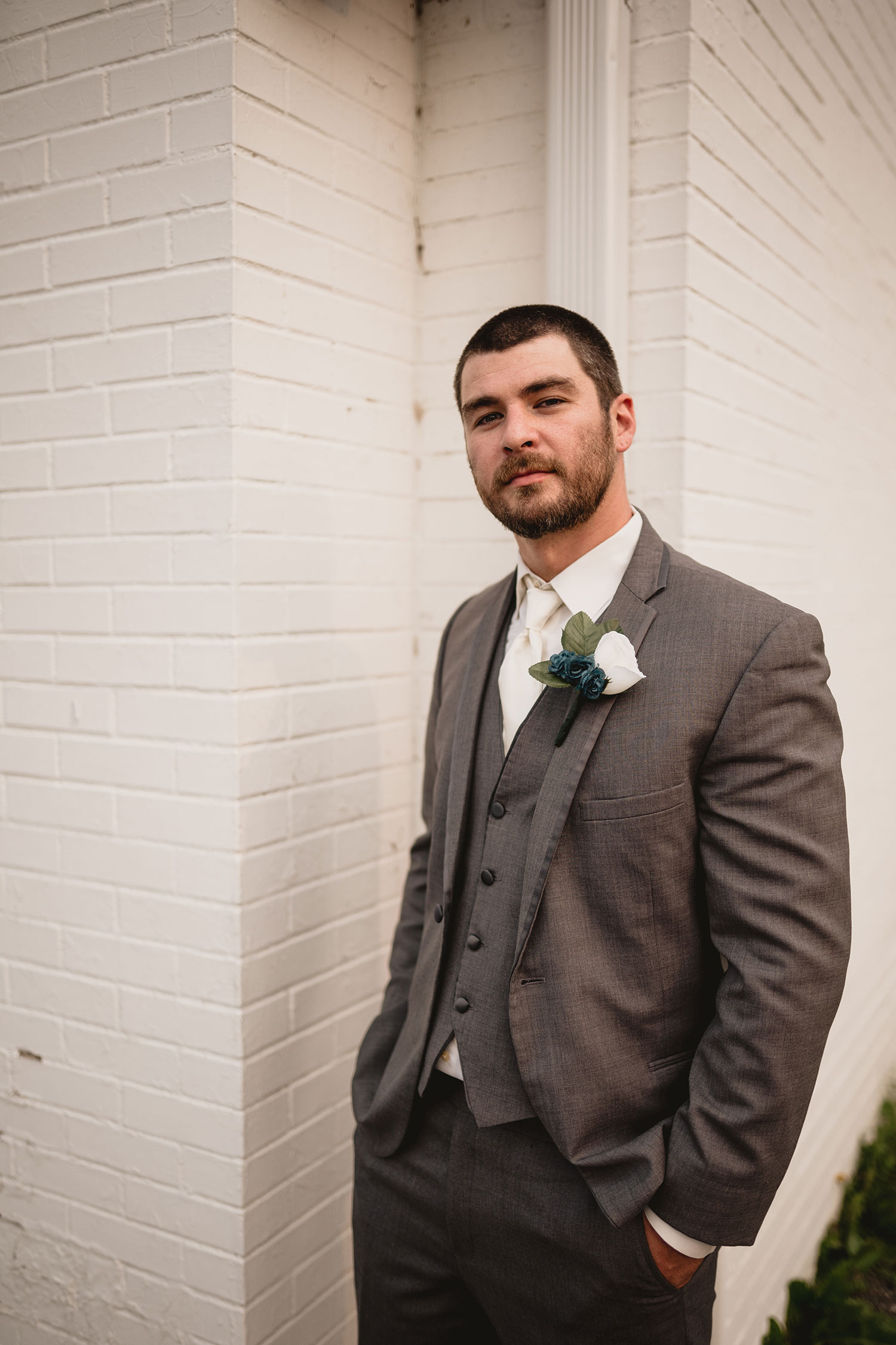 groom-posing-in-front-of-white-brick-wall-decades-event-center-building-desmoines-iowa-raelyn-ramey-photography..jpg