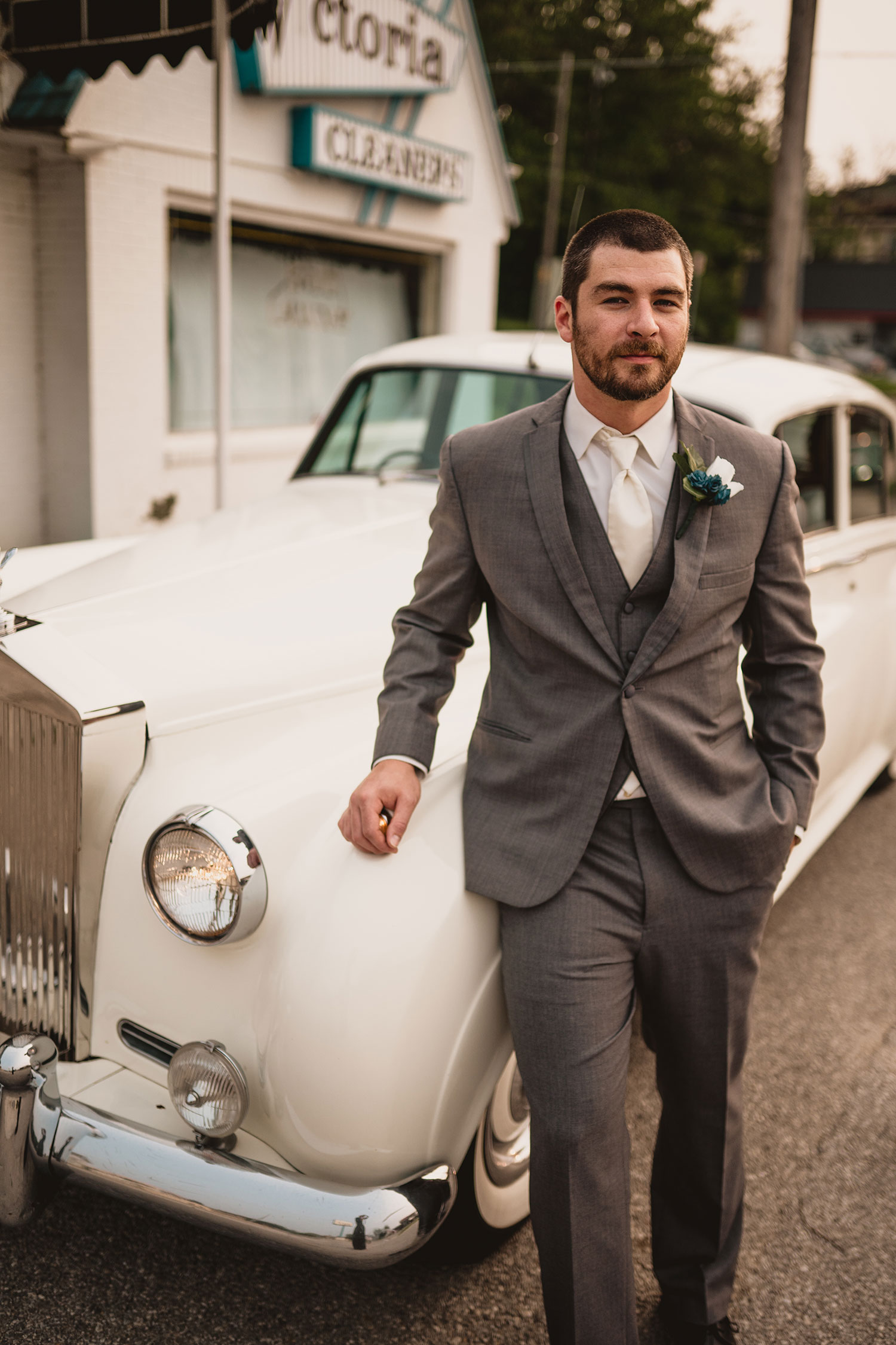 groom-standing-next-to-rolls-royce-decades-event-center-building-desmoines-iowa-raelyn-ramey-photography..jpg