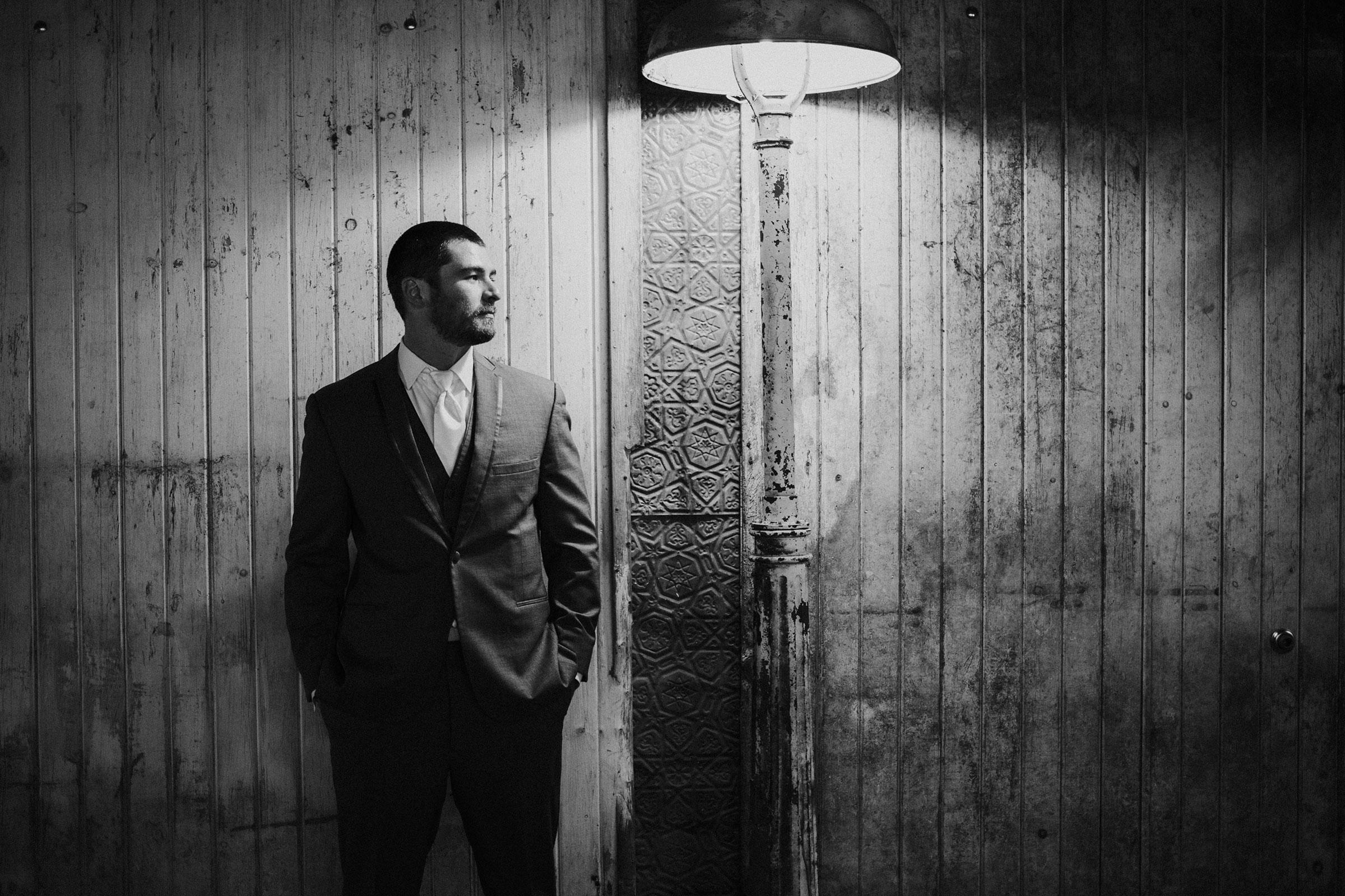 groom-standing-under-light-decades-event-center-building-desmoines-iowa-raelyn-ramey-photography..jpg