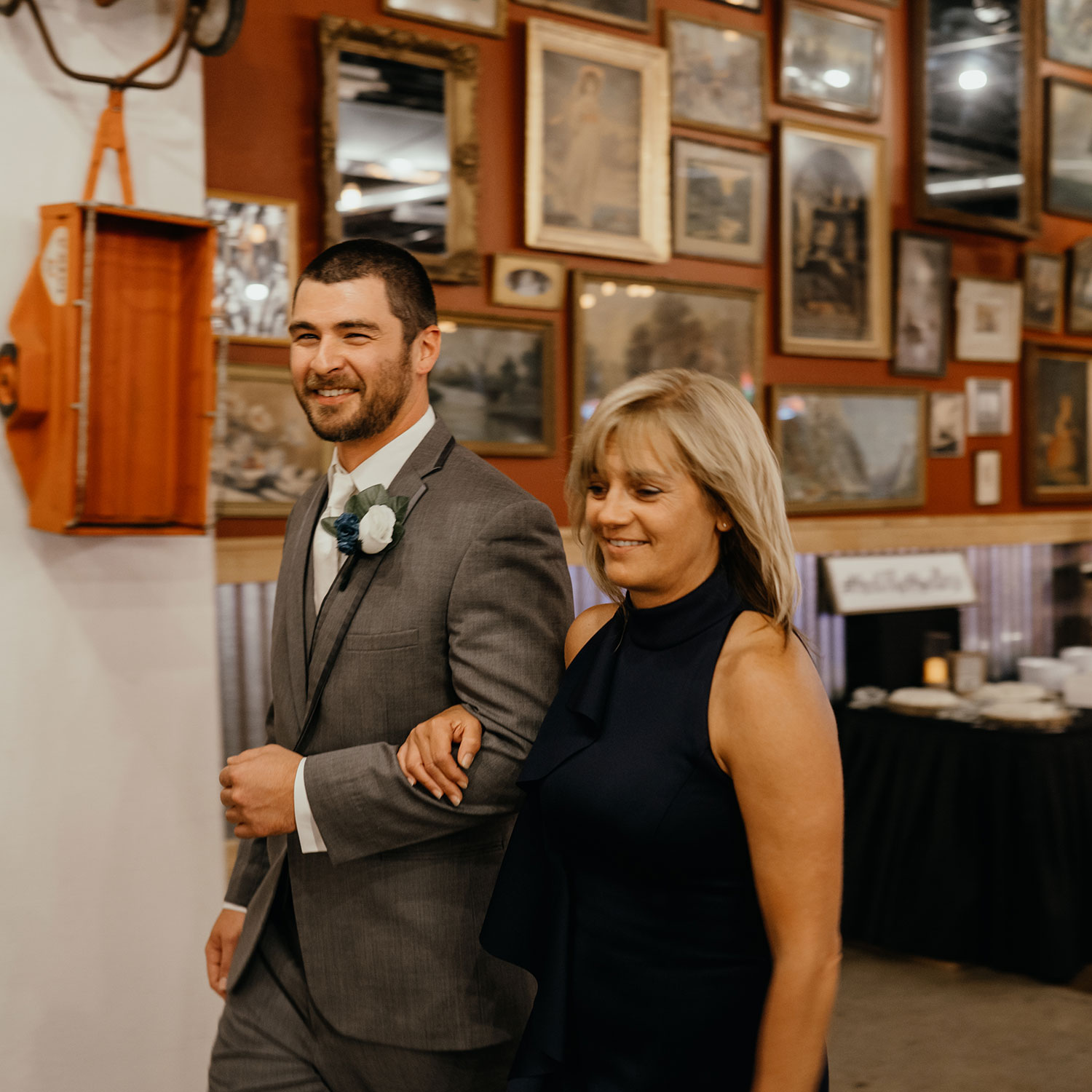 groom-walking-mother-of-bride-down-aisle-decades-event-center-building-desmoines-iowa-raelyn-ramey-photography..jpg