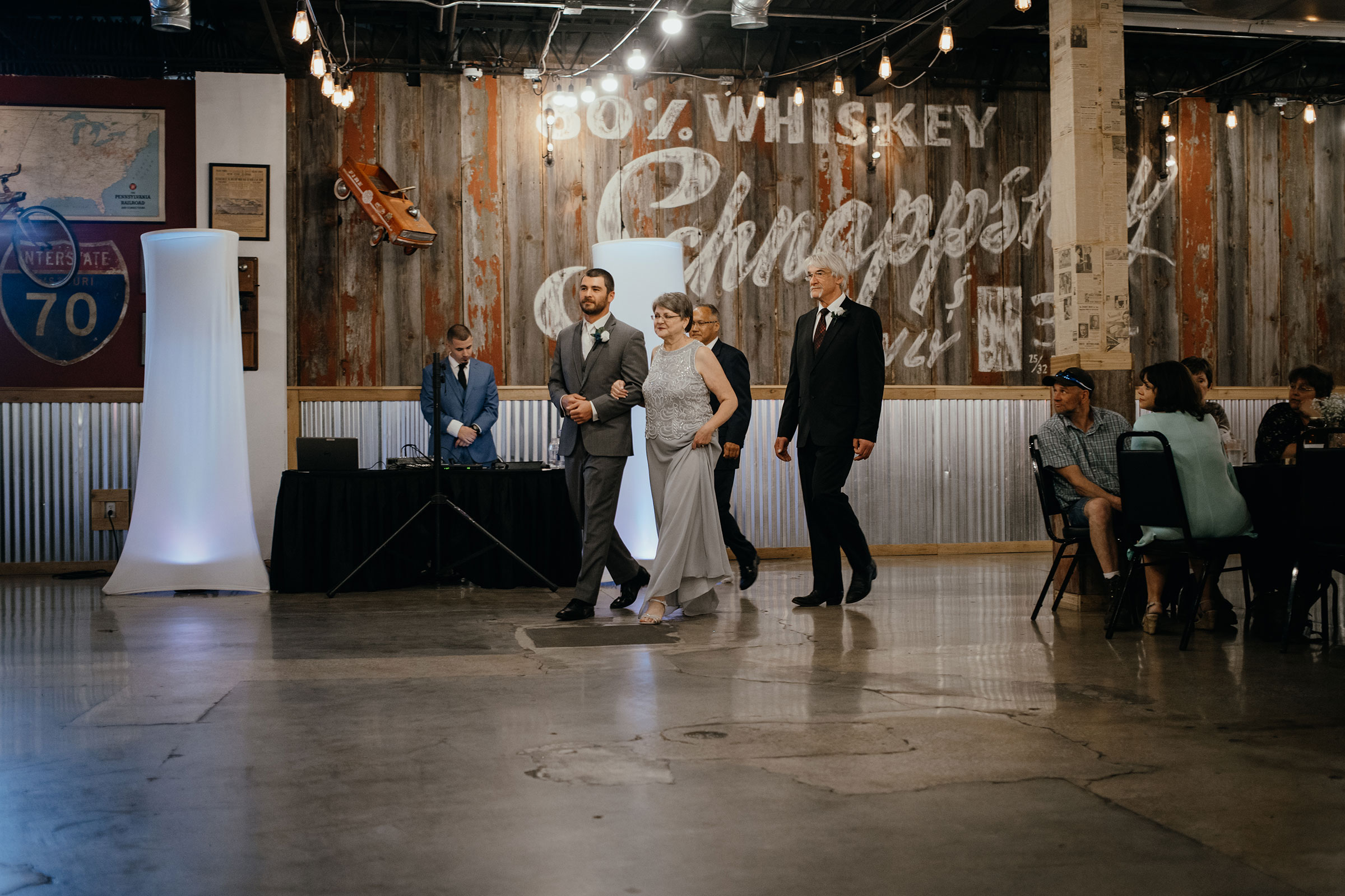 groom-walking-mother-down-aisle-decades-event-center-building-desmoines-iowa-raelyn-ramey-photography..jpg