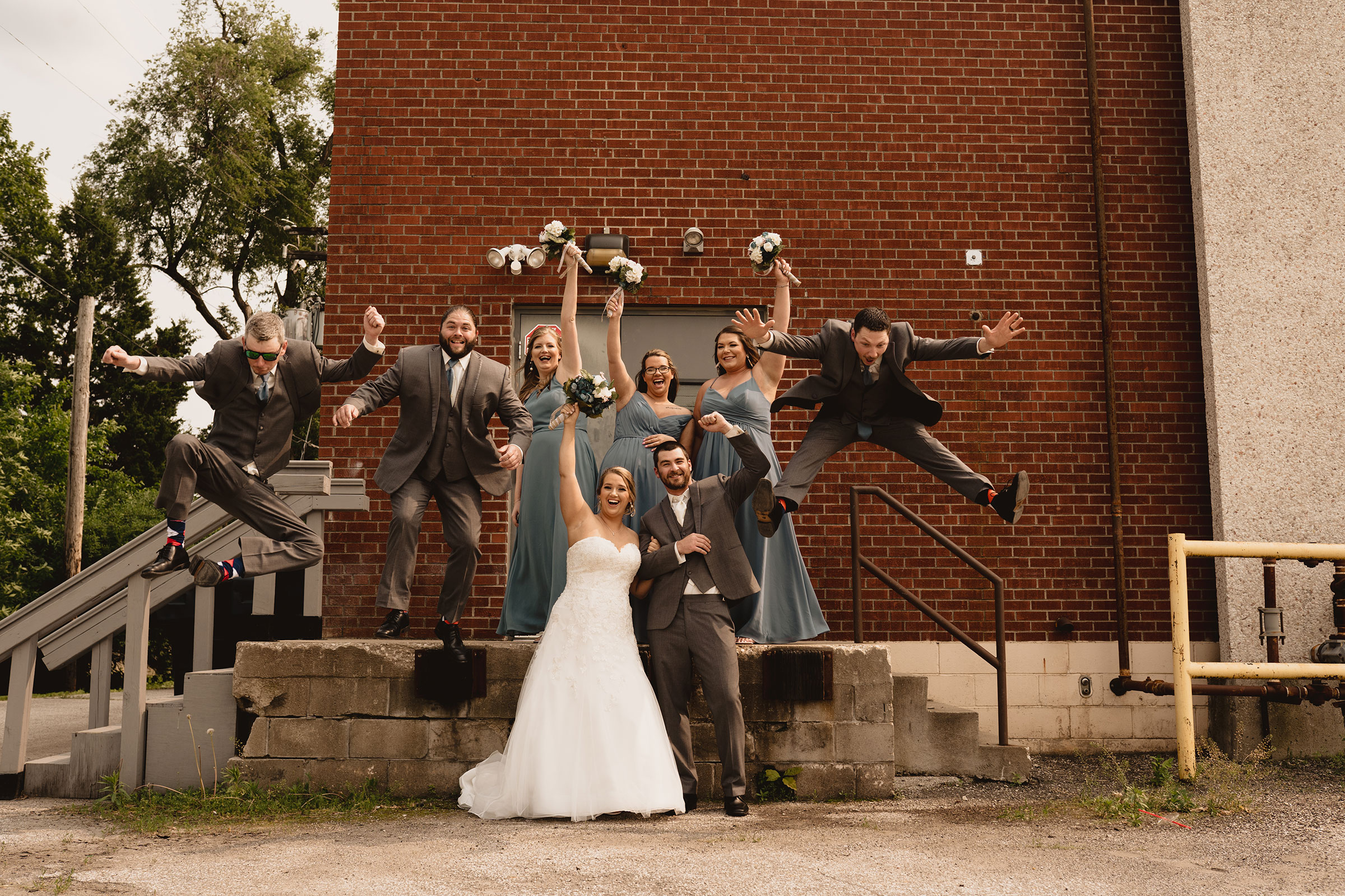 groomsmen-jumping-in-air-decades-event-center-building-desmoines-iowa-raelyn-ramey-photography..jpg