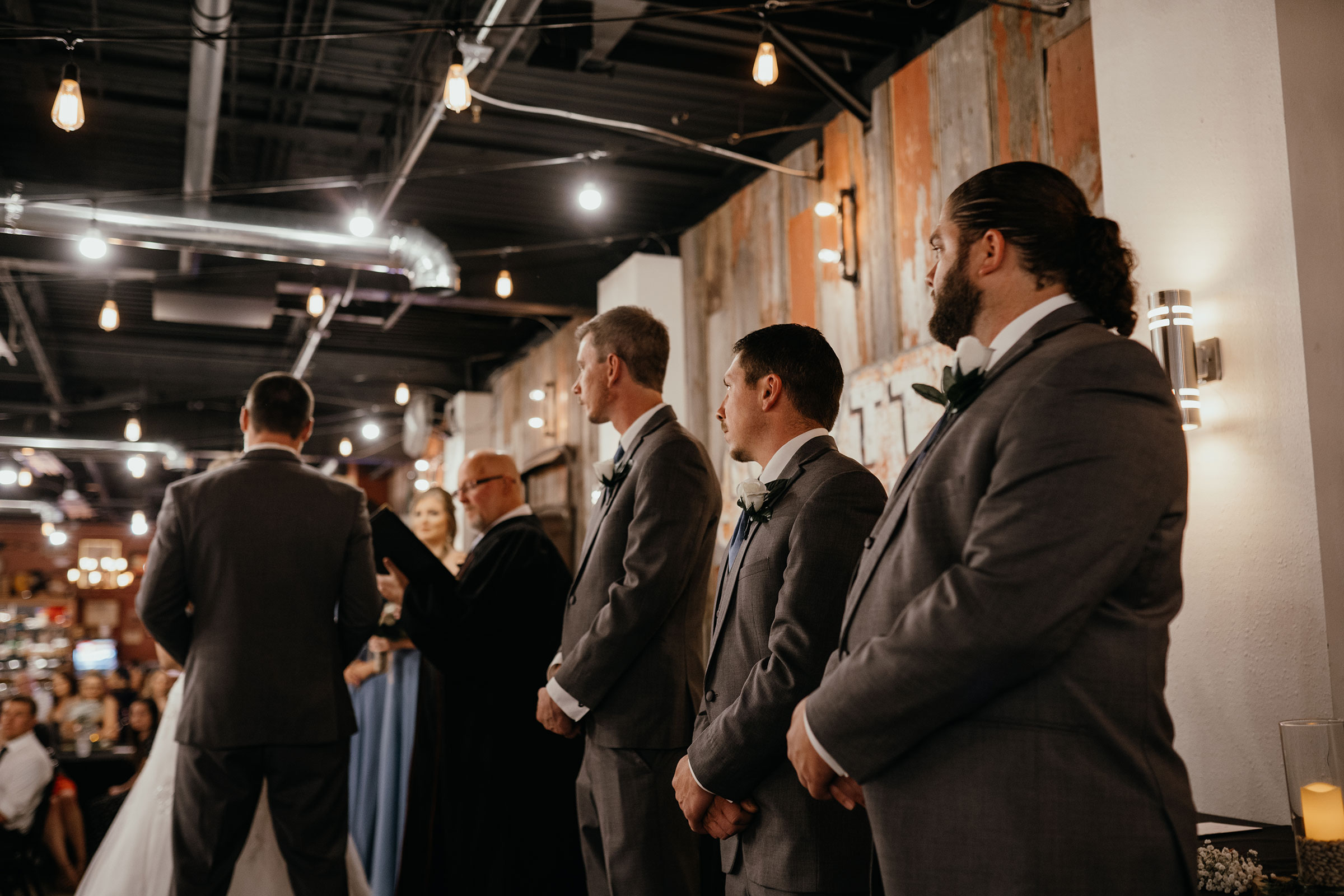 groomsmen-standing-up-during-ceremony-decades-event-center-building-desmoines-iowa-raelyn-ramey-photography..jpg