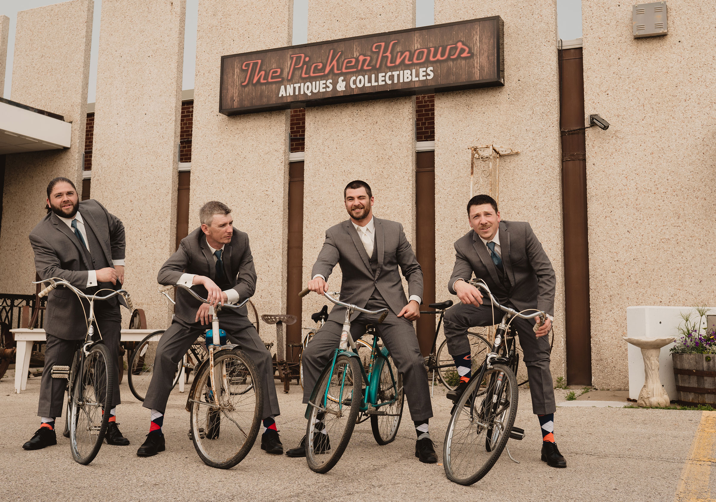 groomsmen-on-bicycles-decades-event-center-building-desmoines-iowa-raelyn-ramey-photography..jpg