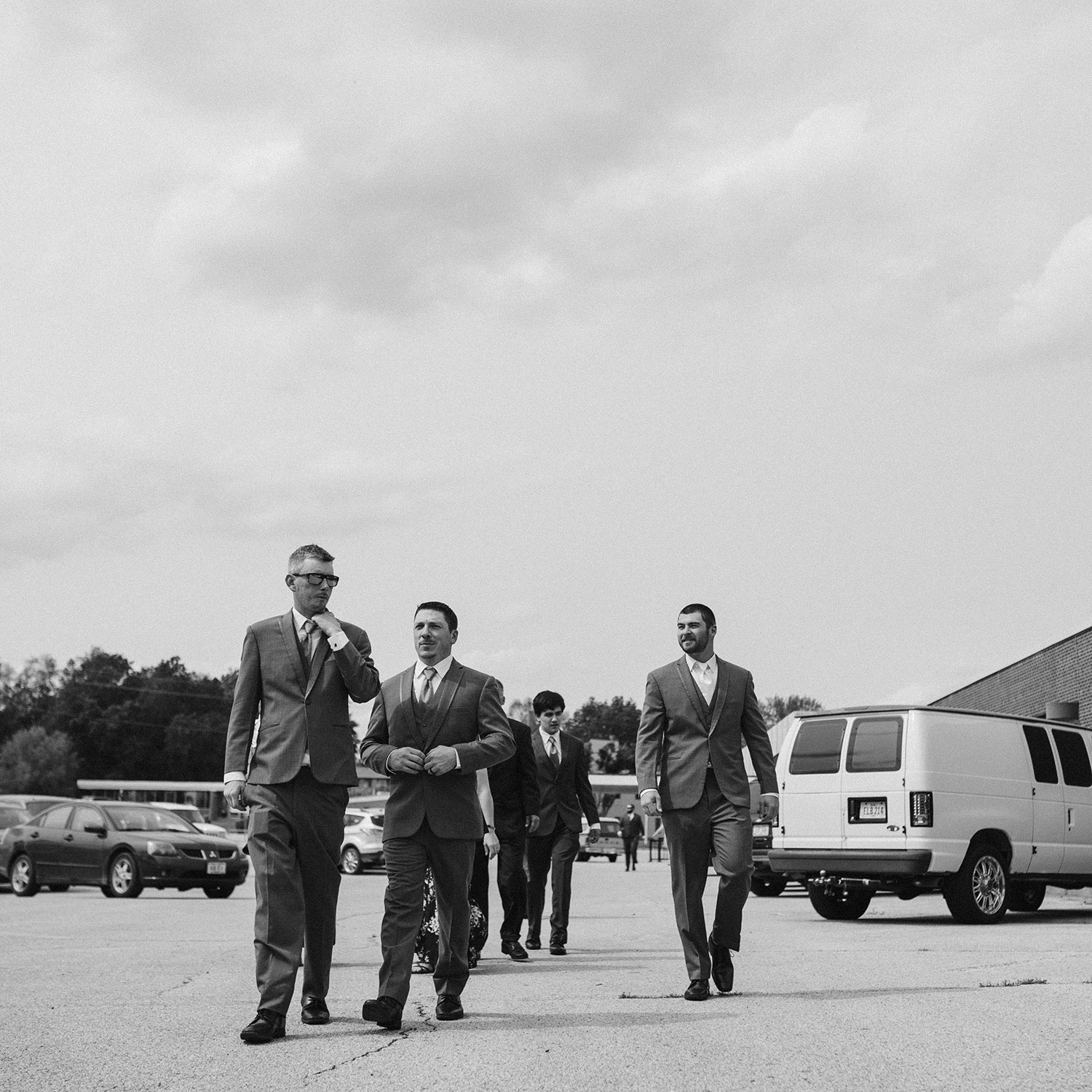 groomsmen-walking-out-of-decades-event-center-building-desmoines-iowa-raelyn-ramey-photography..jpg
