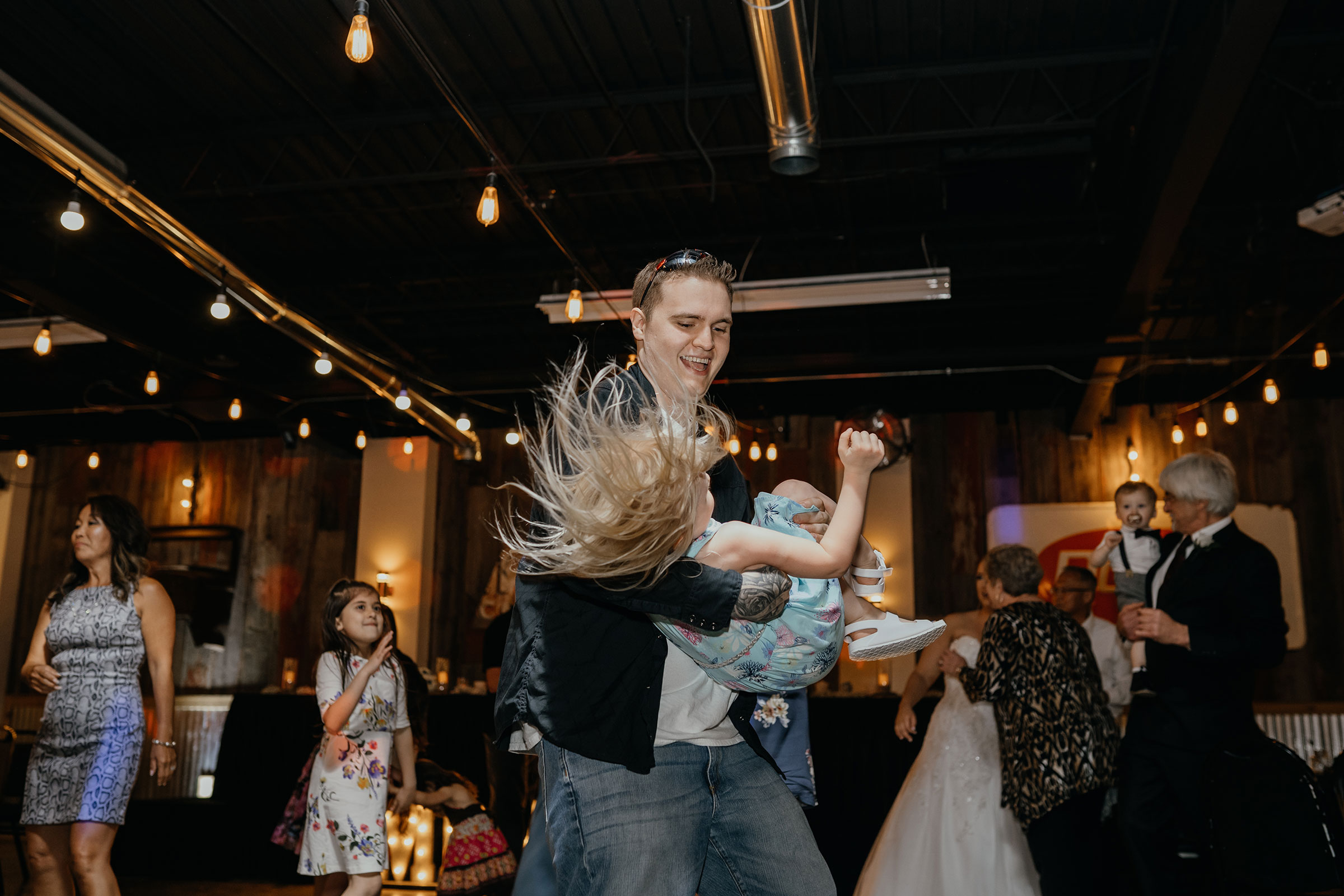 guest-dancing-with-little-girl-decades-event-center-building-desmoines-iowa-raelyn-ramey-photography..jpg