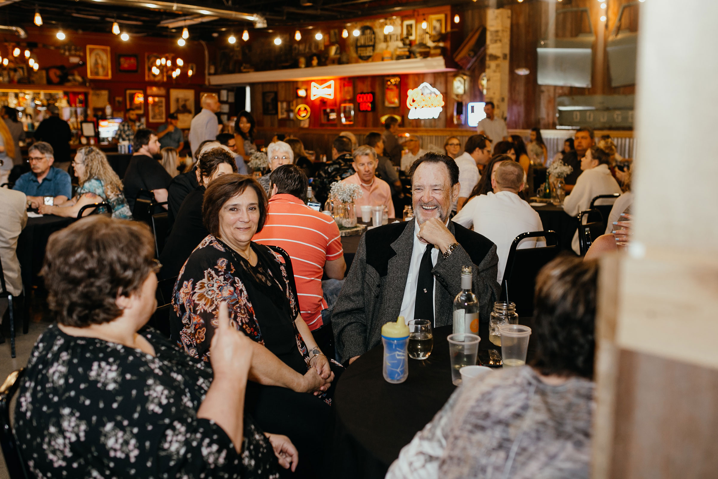 guest-laughing-at-tables-decades-event-center-building-desmoines-iowa-raelyn-ramey-photography..jpg