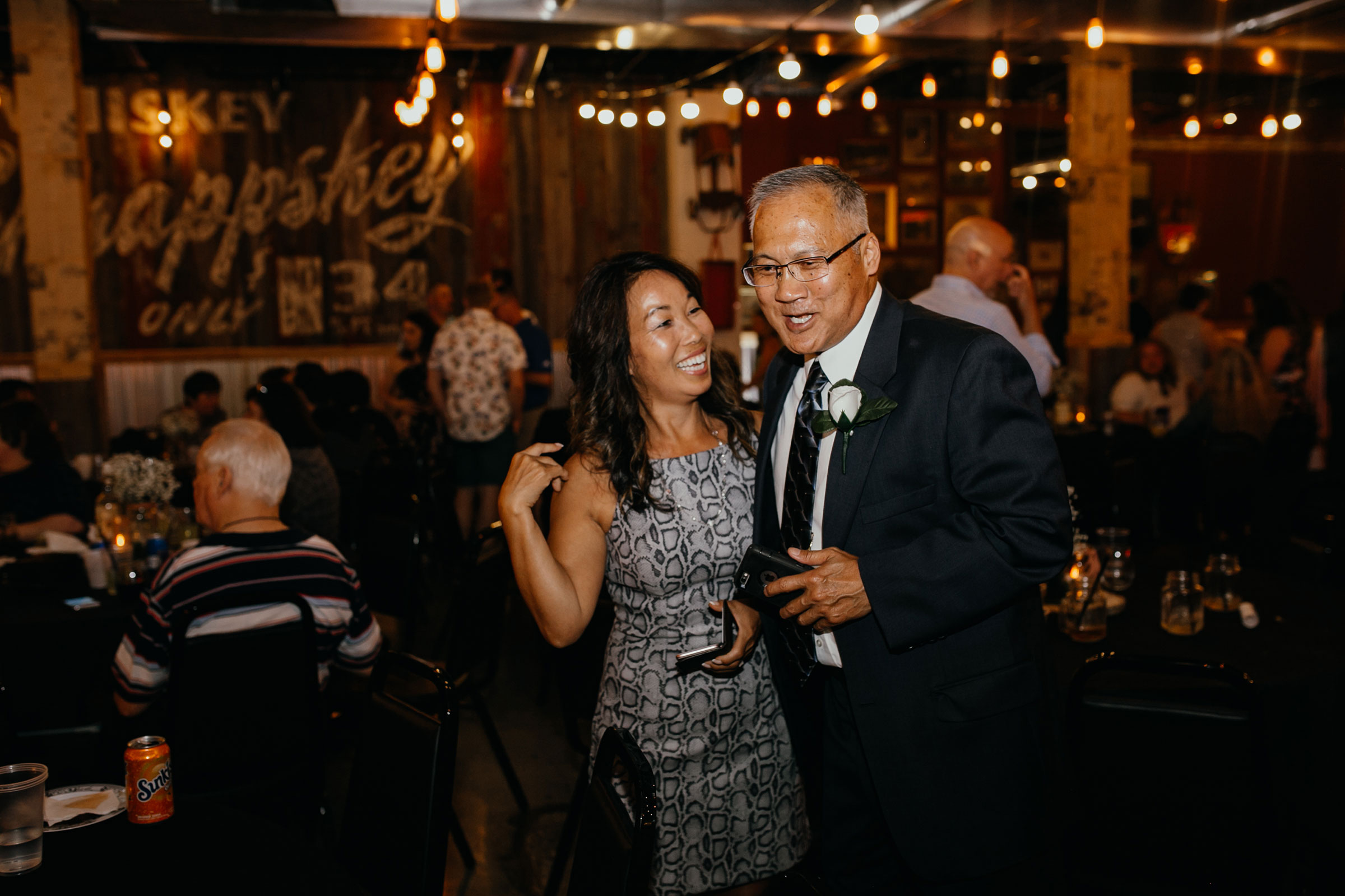 guests-laughing--at-reception-decades-event-center-building-desmoines-iowa-raelyn-ramey-photography..jpg