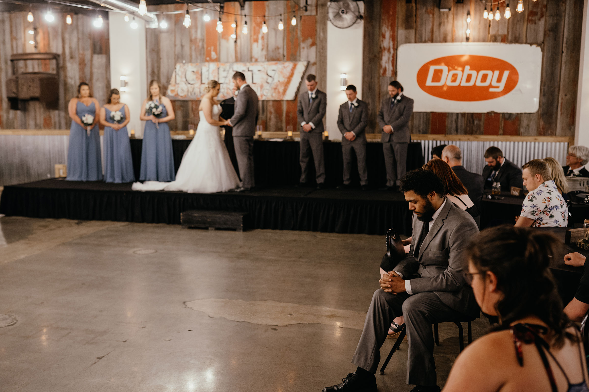 guests-praying-during-ceremony-decades-event-center-building-desmoines-iowa-raelyn-ramey-photography..jpg