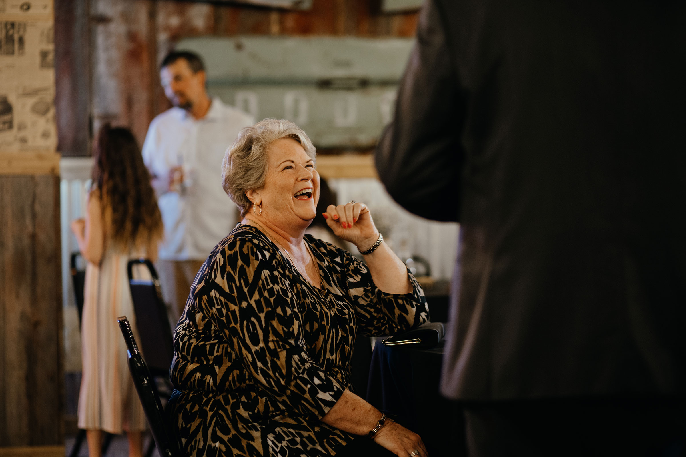 lady-laughing-at-another-guest-decades-event-center-building-desmoines-iowa-raelyn-ramey-photography..jpg