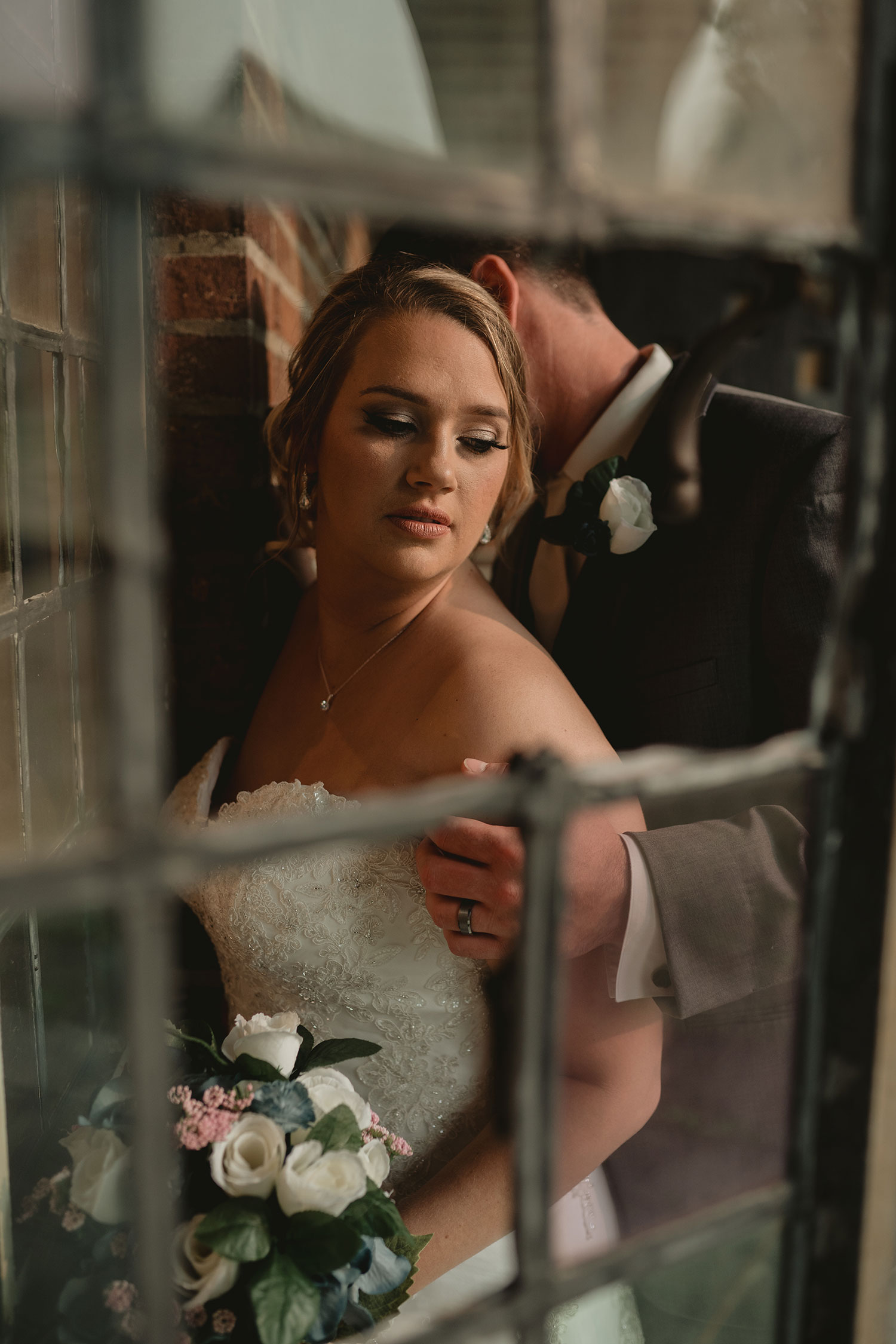 looking-through-an-old-window-at-bride-and-groom-decades-event-center-building-desmoines-iowa-raelyn-ramey-photography..jpg