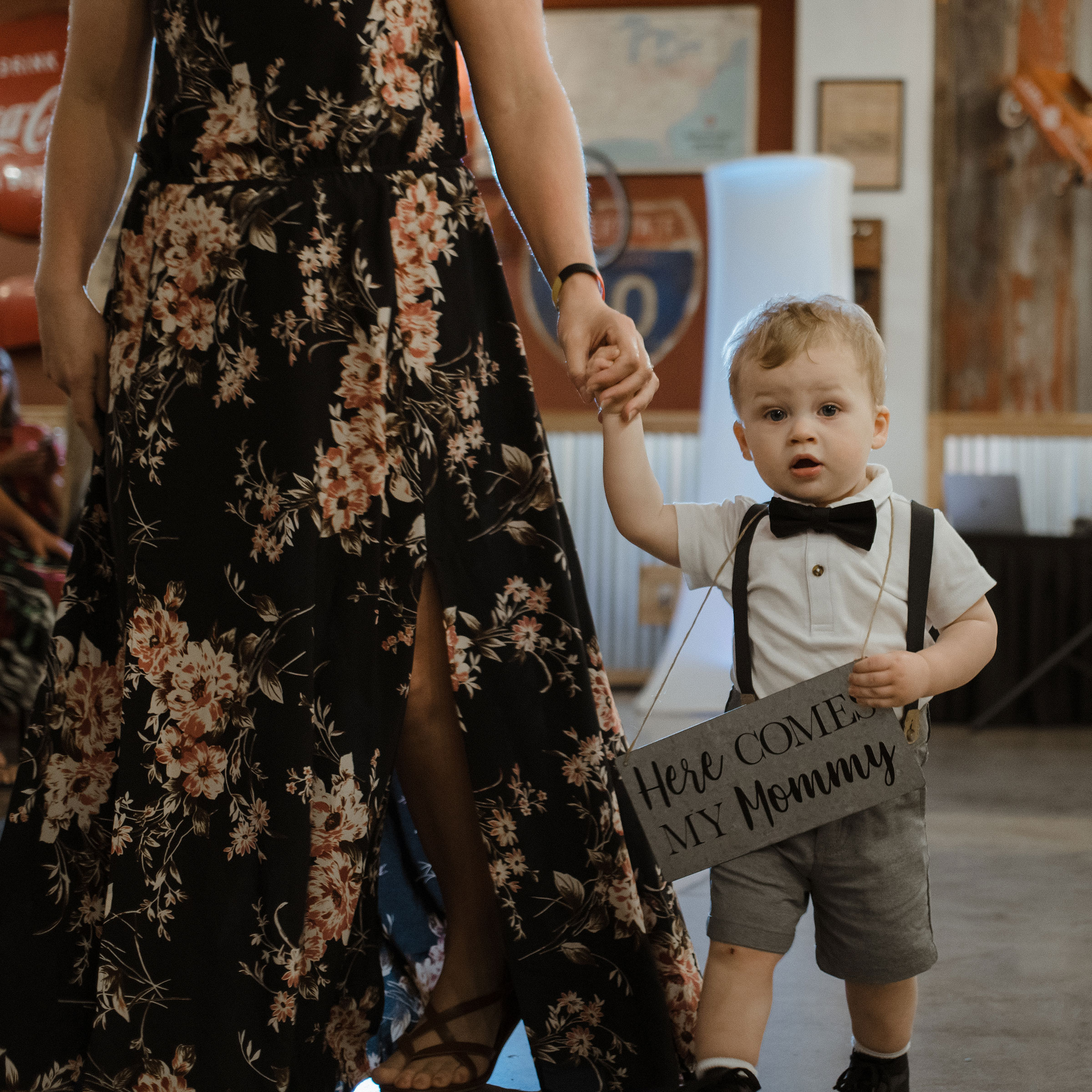 little-boy-walking-down-aisle-with-sign-decades-event-center-building-desmoines-iowa-raelyn-ramey-photography.jpg