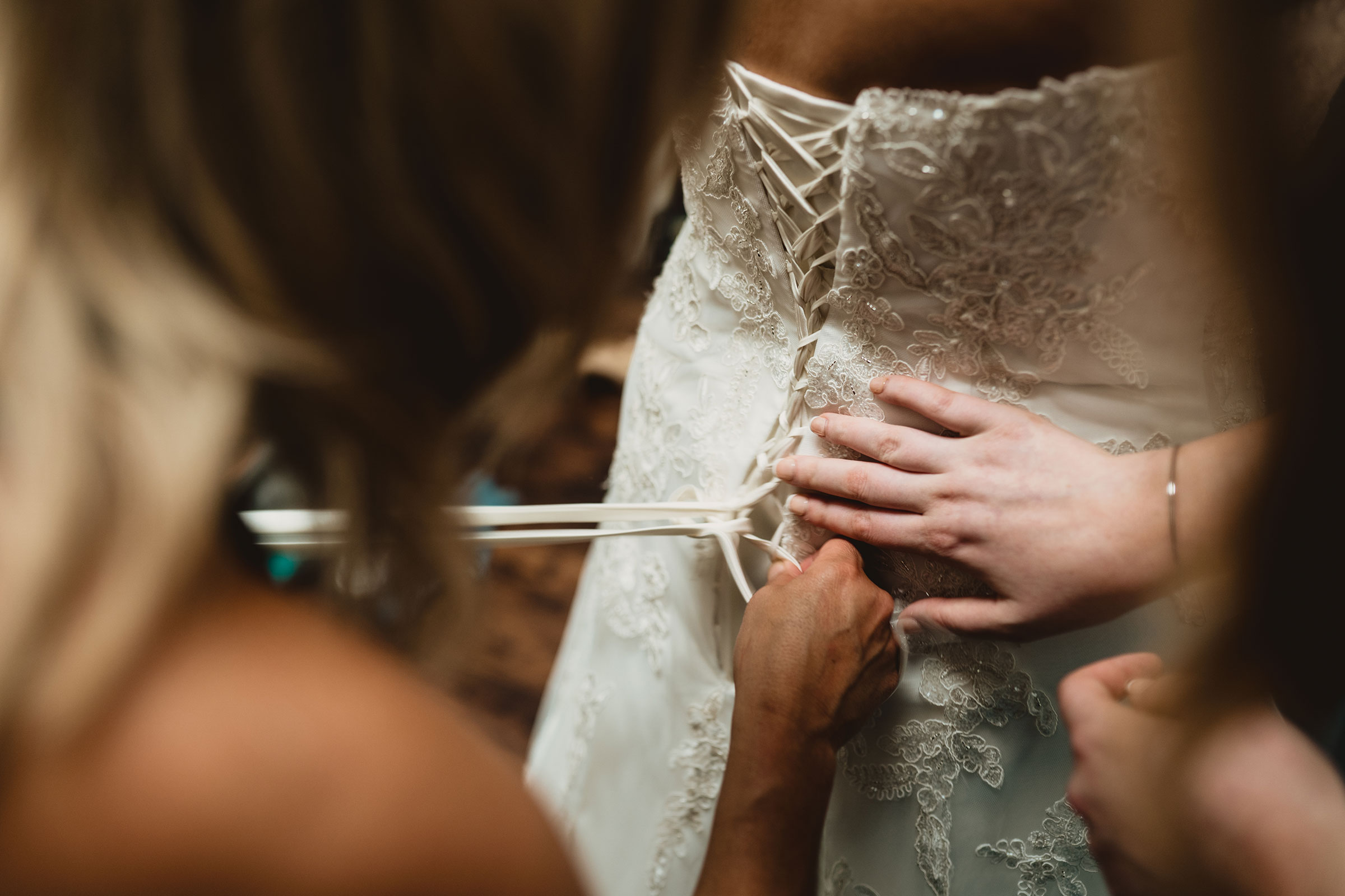 mother-helping-bride-get-ready-decades-event-center-building-desmoines-iowa-raelyn-ramey-photography..jpg