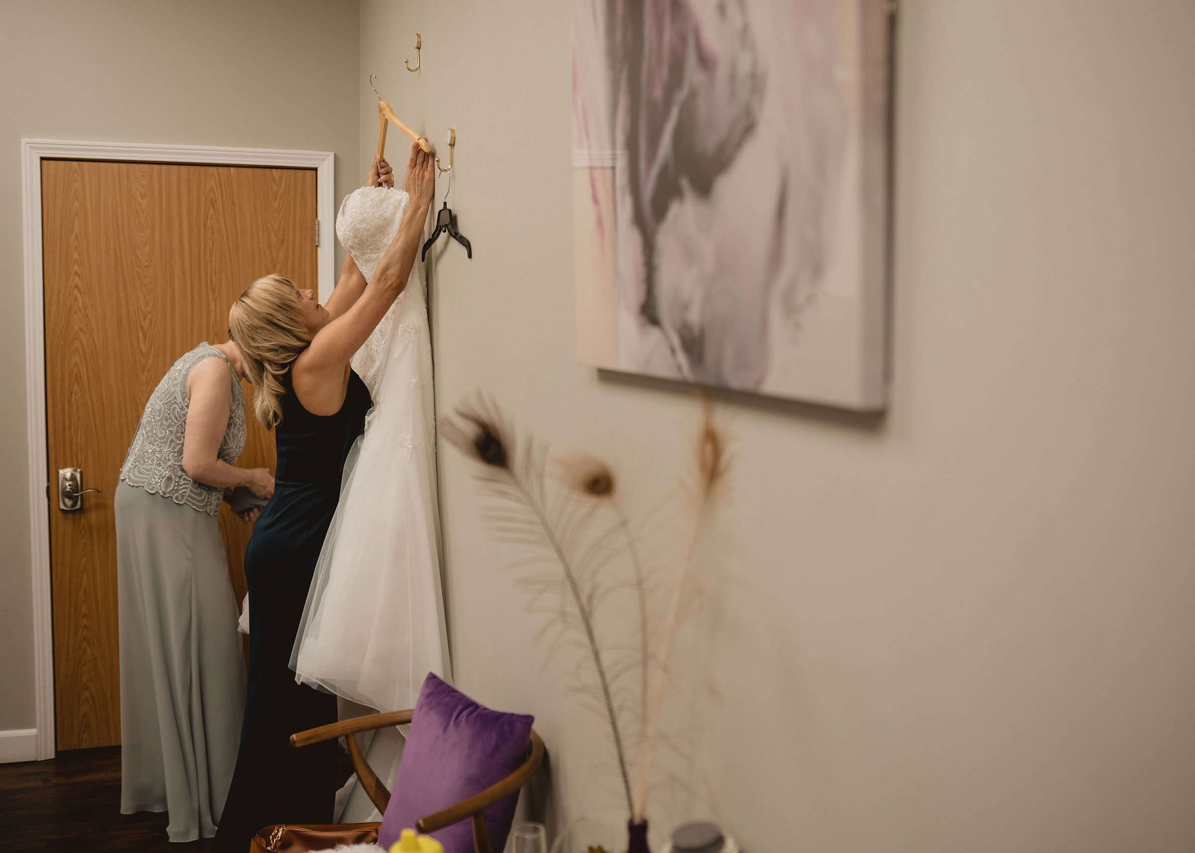 mother-of-bride-getting-bridal-dress-off-wall-decades-event-center-building-desmoines-iowa-raelyn-ramey-photography..jpg