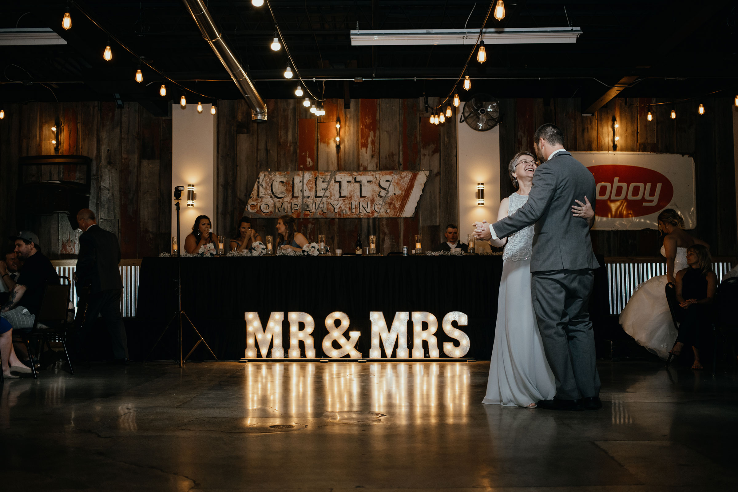 mother-of-groom-dancing-with-son-smiling-decades-event-center-building-desmoines-iowa-raelyn-ramey-photography..jpg
