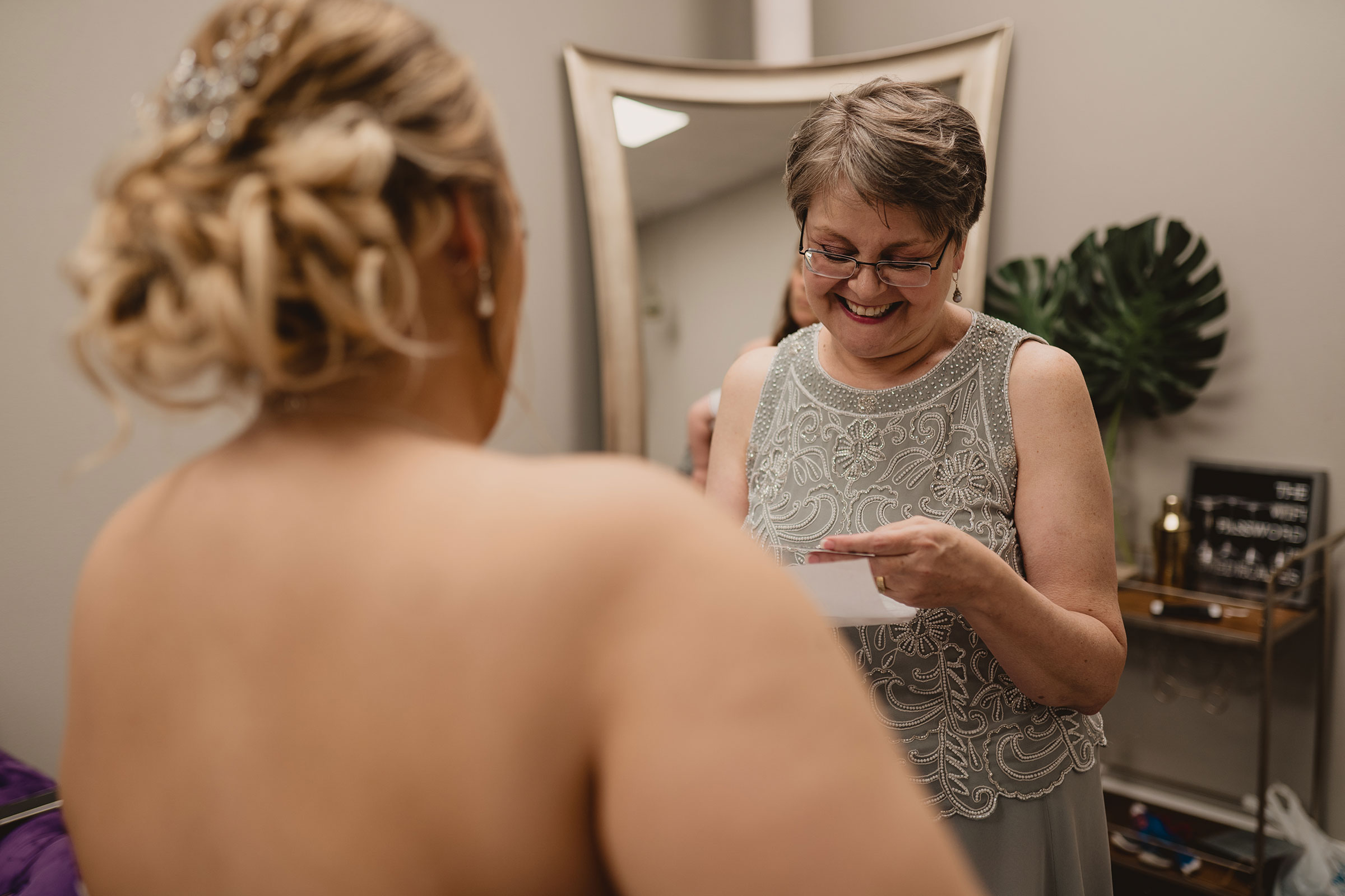 mother-of-groom-getting-gift-from-bride-decades-event-center-building-desmoines-iowa-raelyn-ramey-photography..jpg