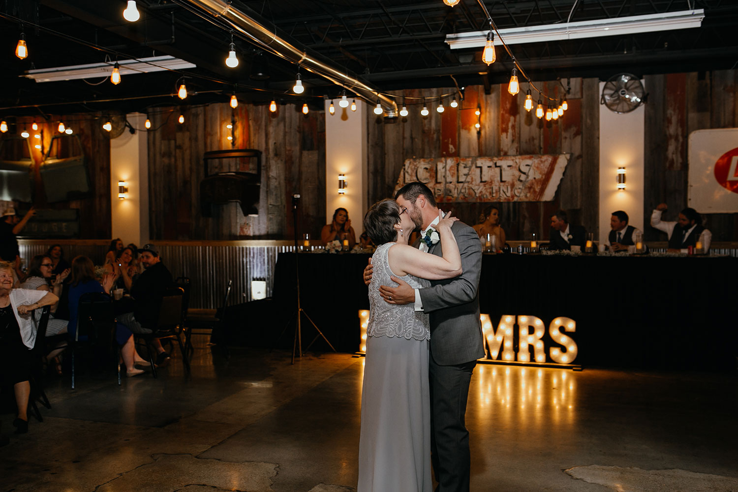 mother-of-groom-kissing-groom-decades-event-center-building-desmoines-iowa-raelyn-ramey-photography..jpg