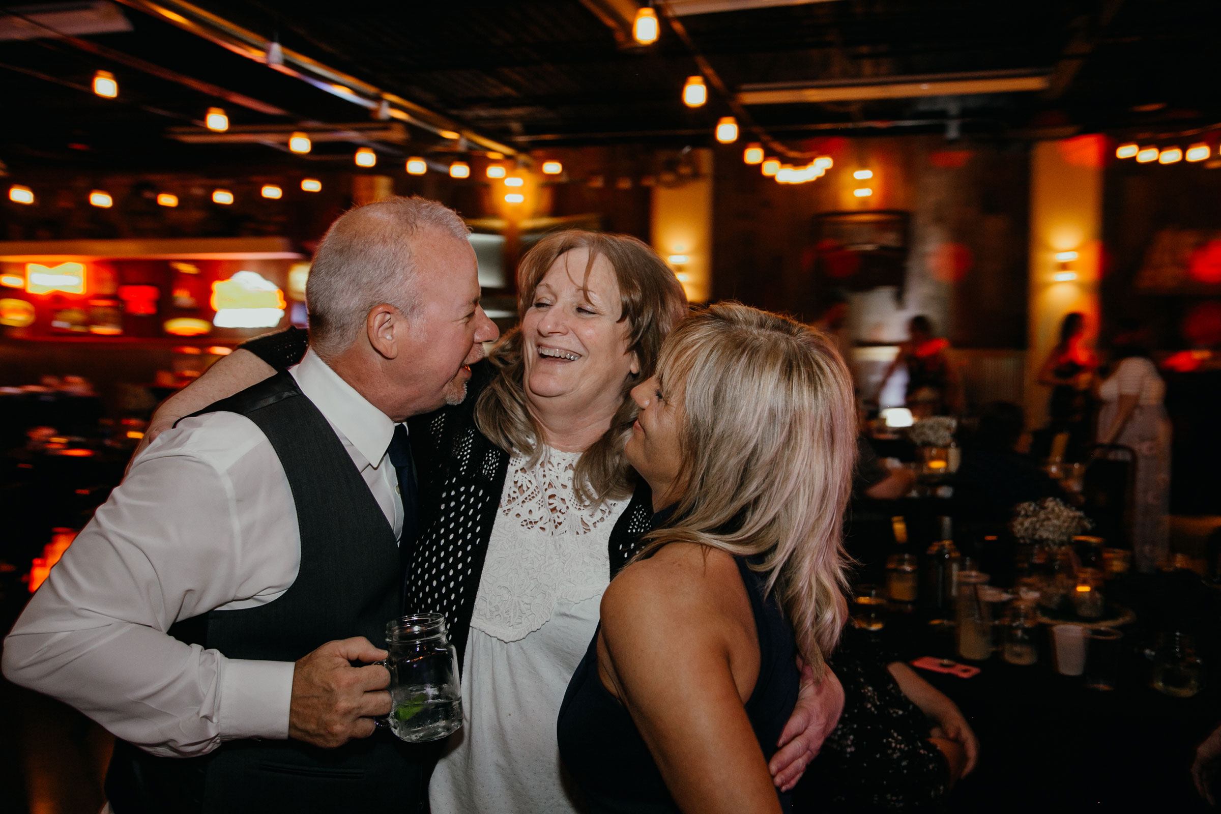 parents-talking-with-guest-laughing-decades-event-center-building-desmoines-iowa-raelyn-ramey-photography..jpg