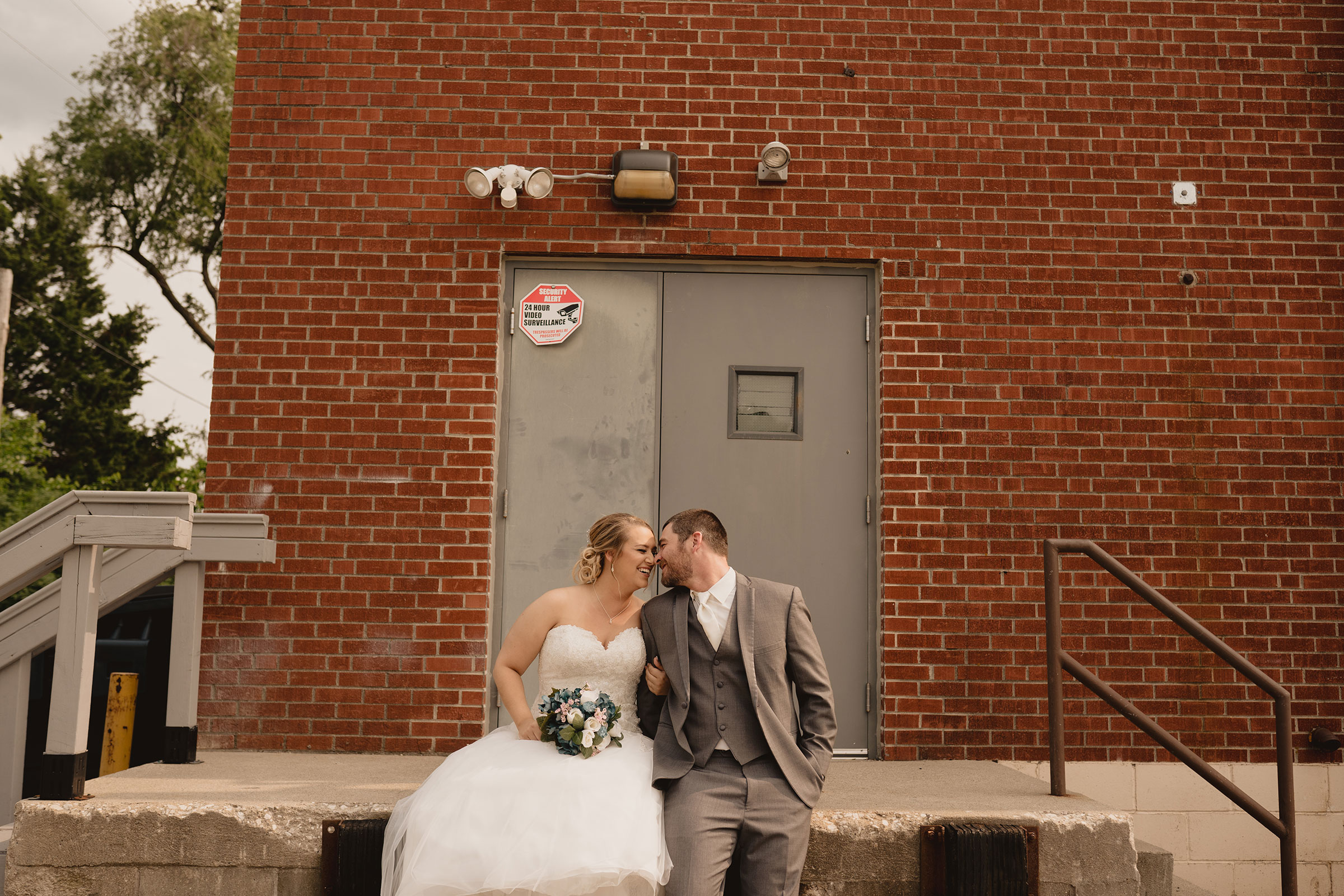 wedding-couple-laughing-sitting-on-concrete-decades-event-center-building-desmoines-iowa-raelyn-ramey-photography..jpg