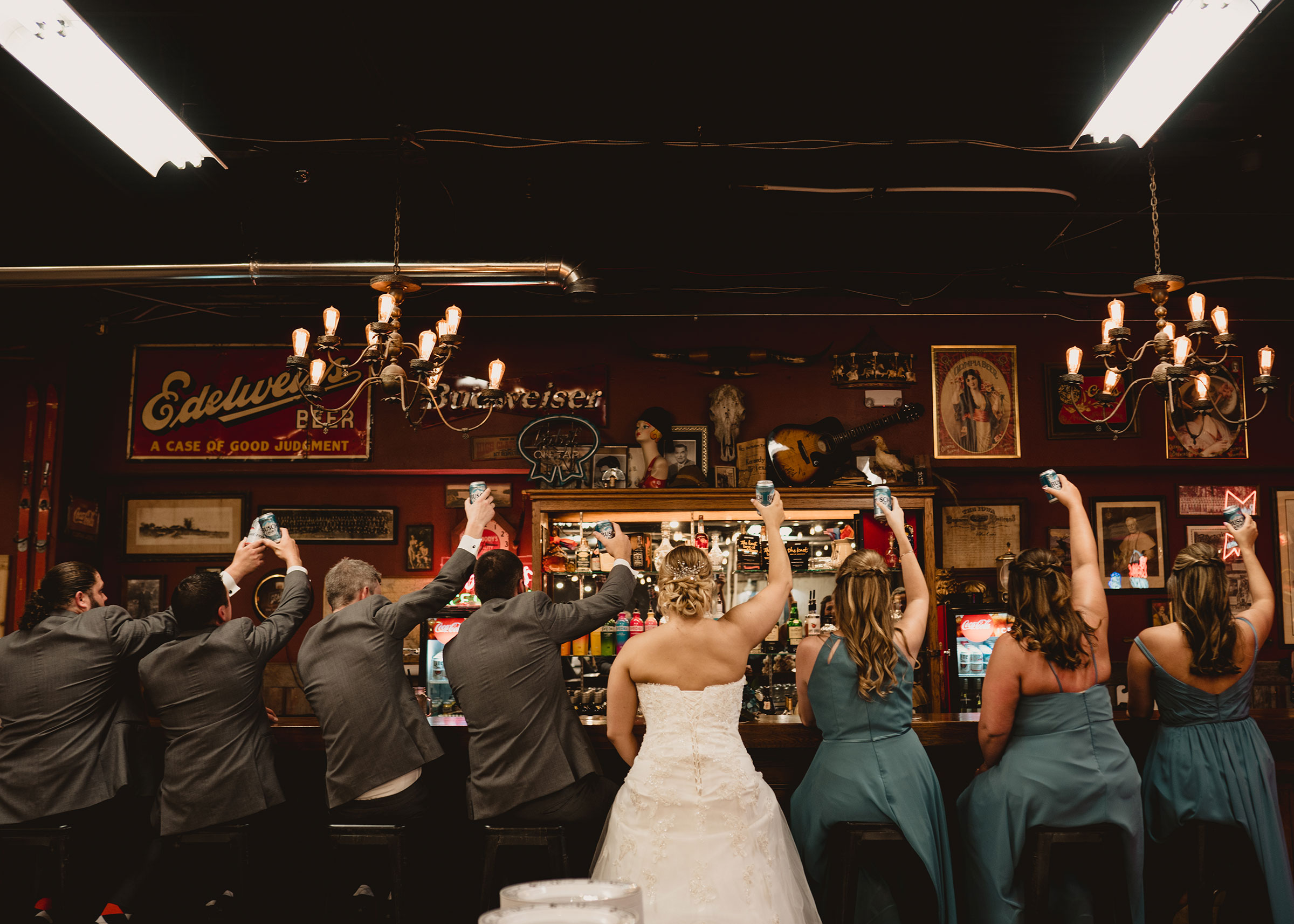 wedding-party-sitting-at-bar-decades-event-center-building-desmoines-iowa-raelyn-ramey-photography..jpg