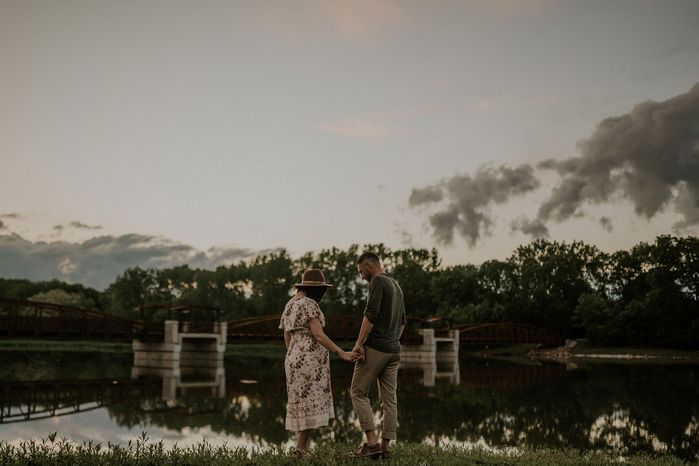 husband-and-pregnant-wife-holding-hands-looking-down-at-water--maternity-desmoines-iowa-raelyn-ramey-photography.jpg