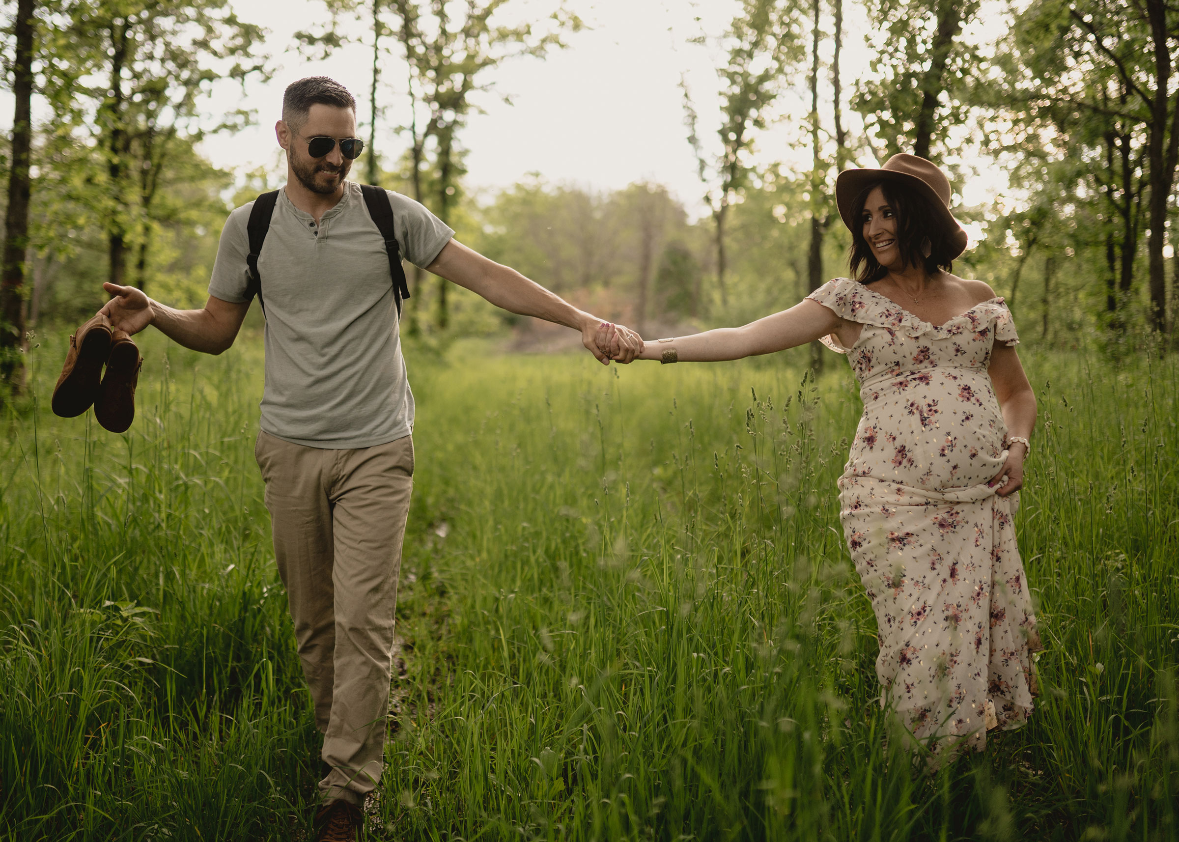 husband-holding-pregnant-wifes-shoes-while-walking-out-of-woods-maternity-desmoines-iowa-raelyn-ramey-photography.jpg