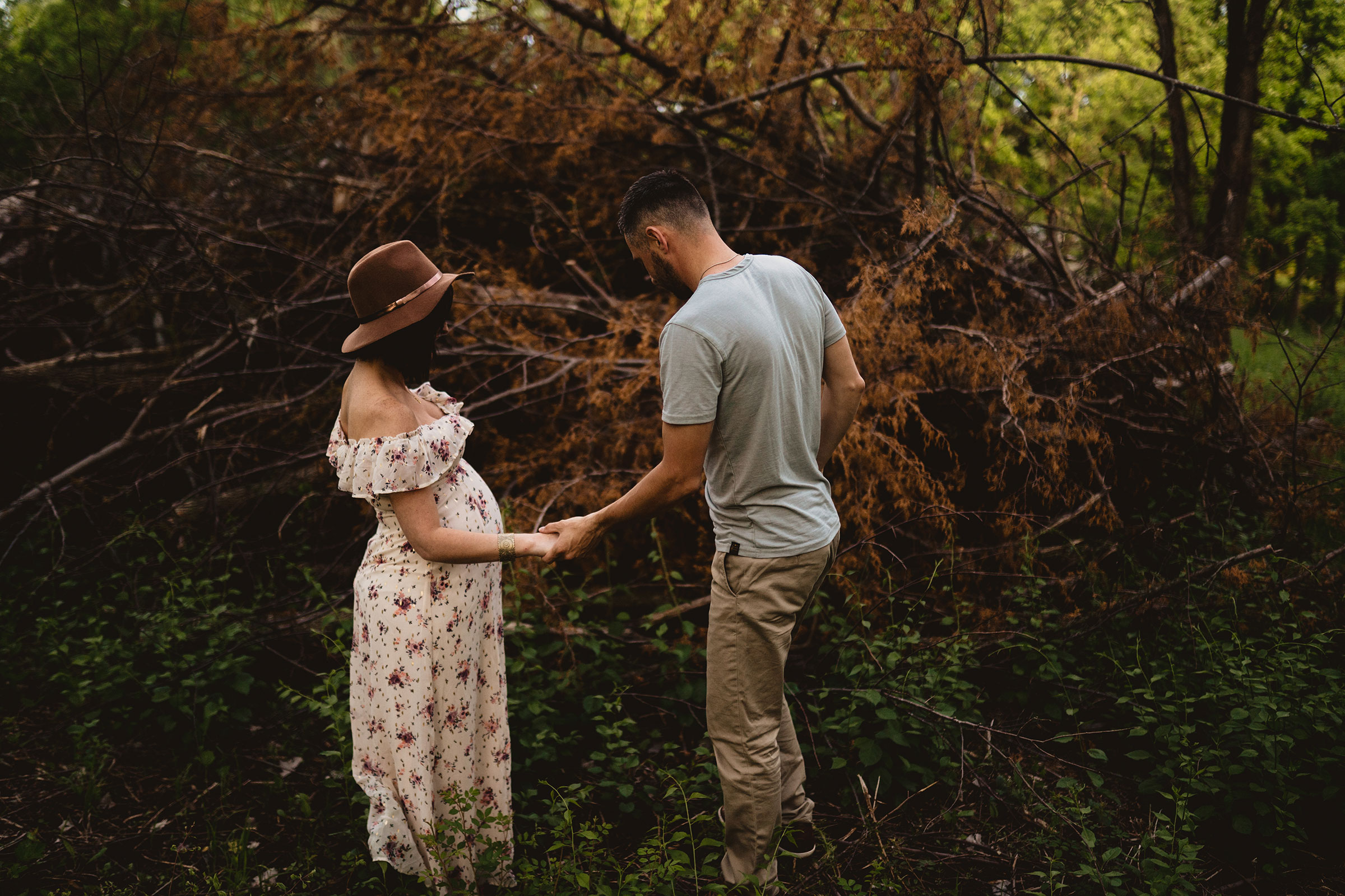 pregnant-wife-and-husband-holding-hands-next-to-brush-pile-maternity-desmoines-iowa-raelyn-ramey-photography.jpg